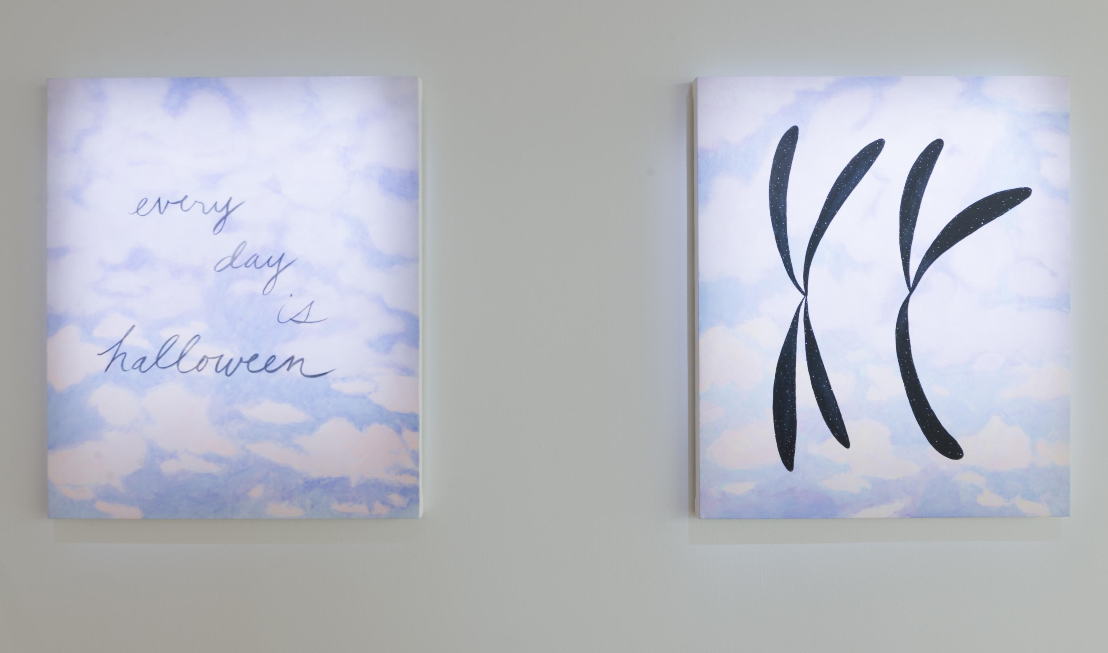 """Two paintings of idyllic cloudy blue skies hang side by side. One reads """"every day is halloween"""" in cursive, the other has two shapes like an """"X"""" and a """"Y,"""" like chromosomes."""
