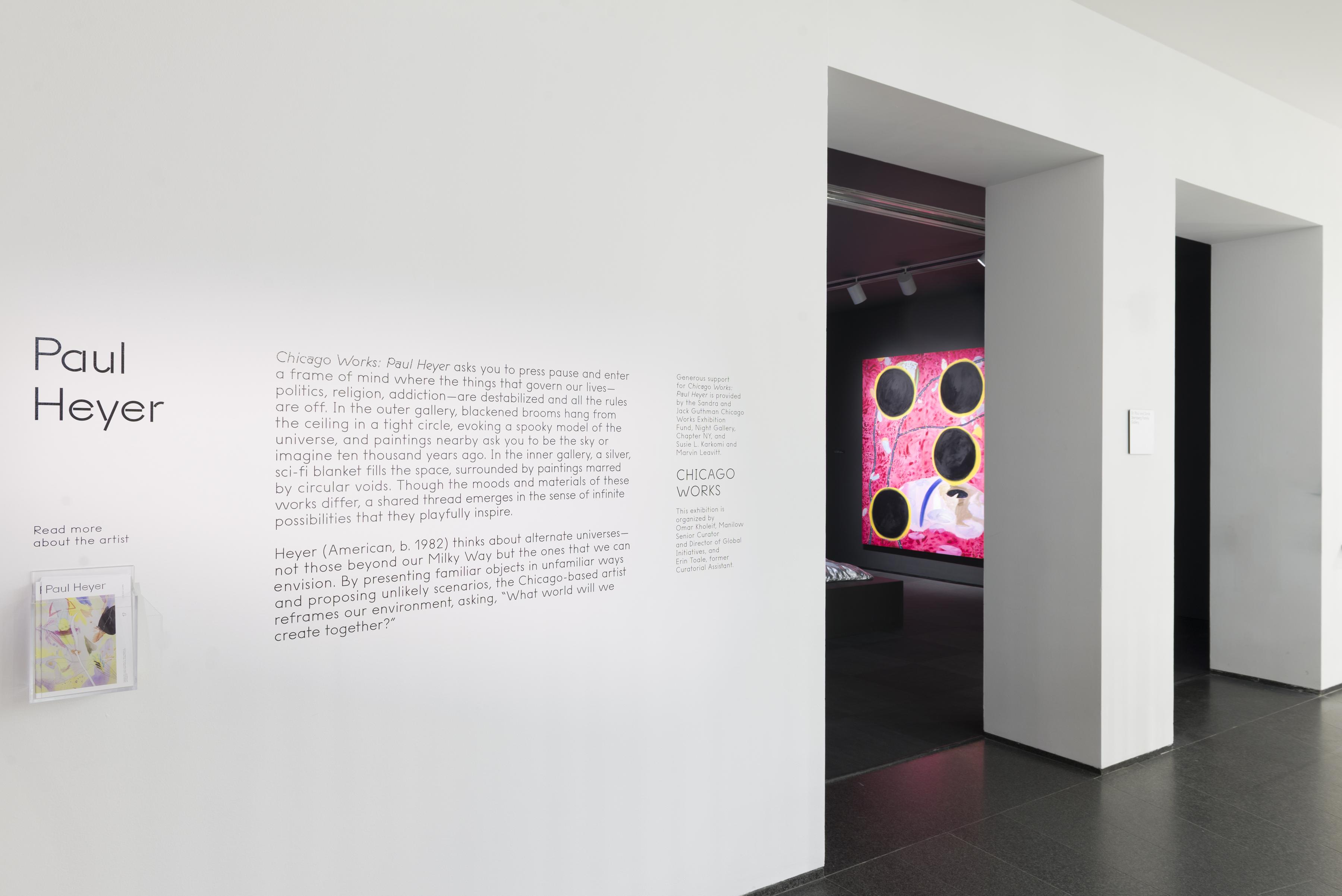 """An exterior shot of an art gallery reads """"Paul Heyer"""" in large text with smaller text introducing the exhibit. The gallery is dark, with a large red painting illuminated on the wall."""