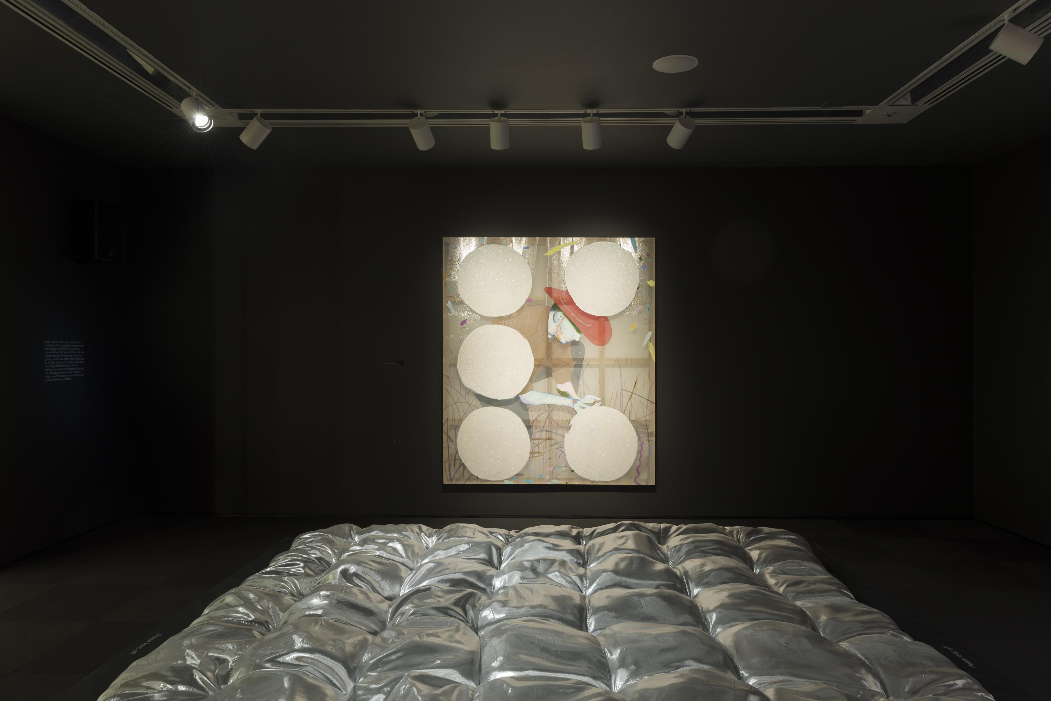A darkened gallery features a metallic silver blanket in the foreground and a painting of a cowboy crouching in the background.