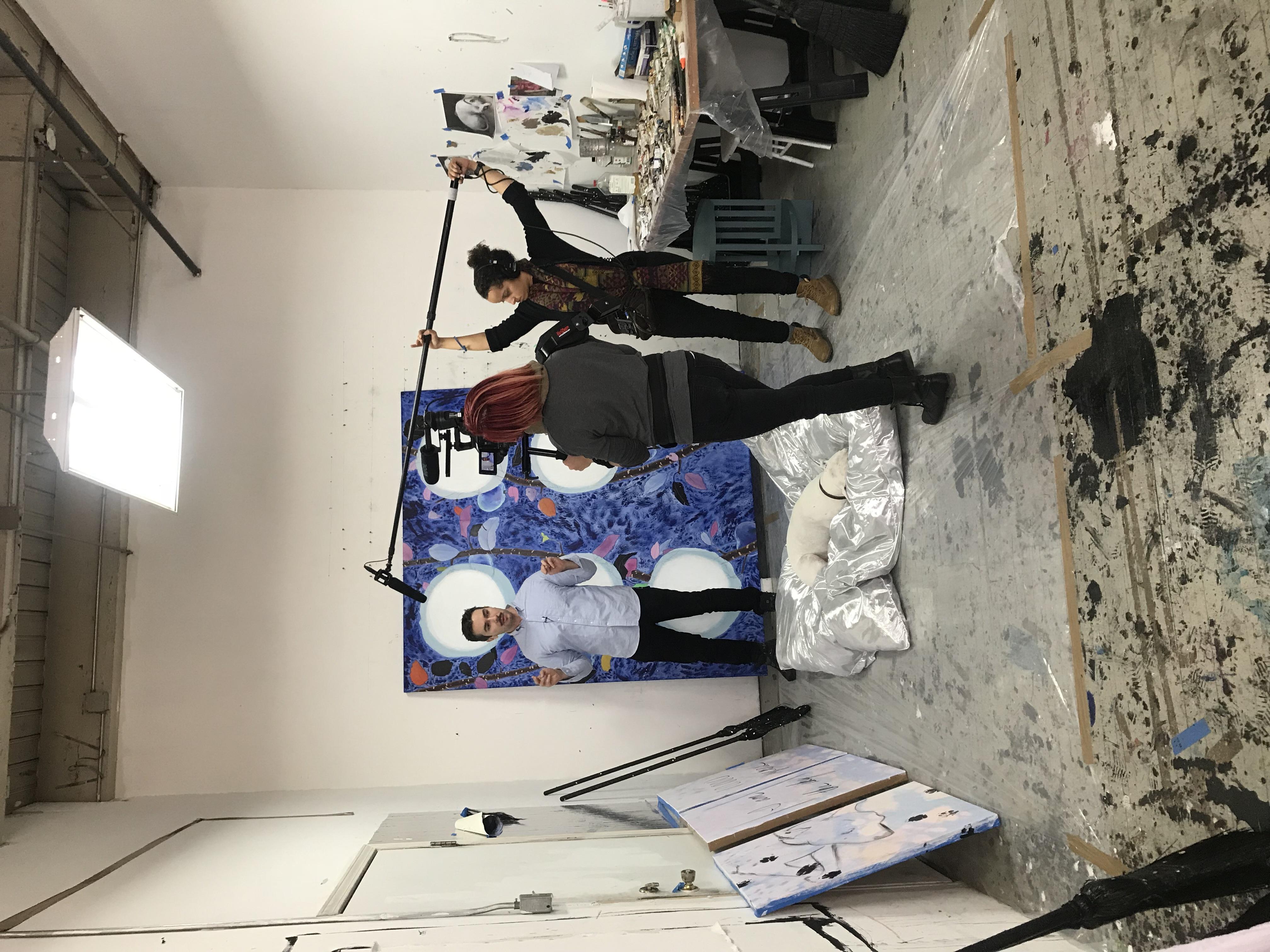 Two young feminine people hold recording equipment while a young dark-haired man speaks. They are in an artist's workspace with various artworks.