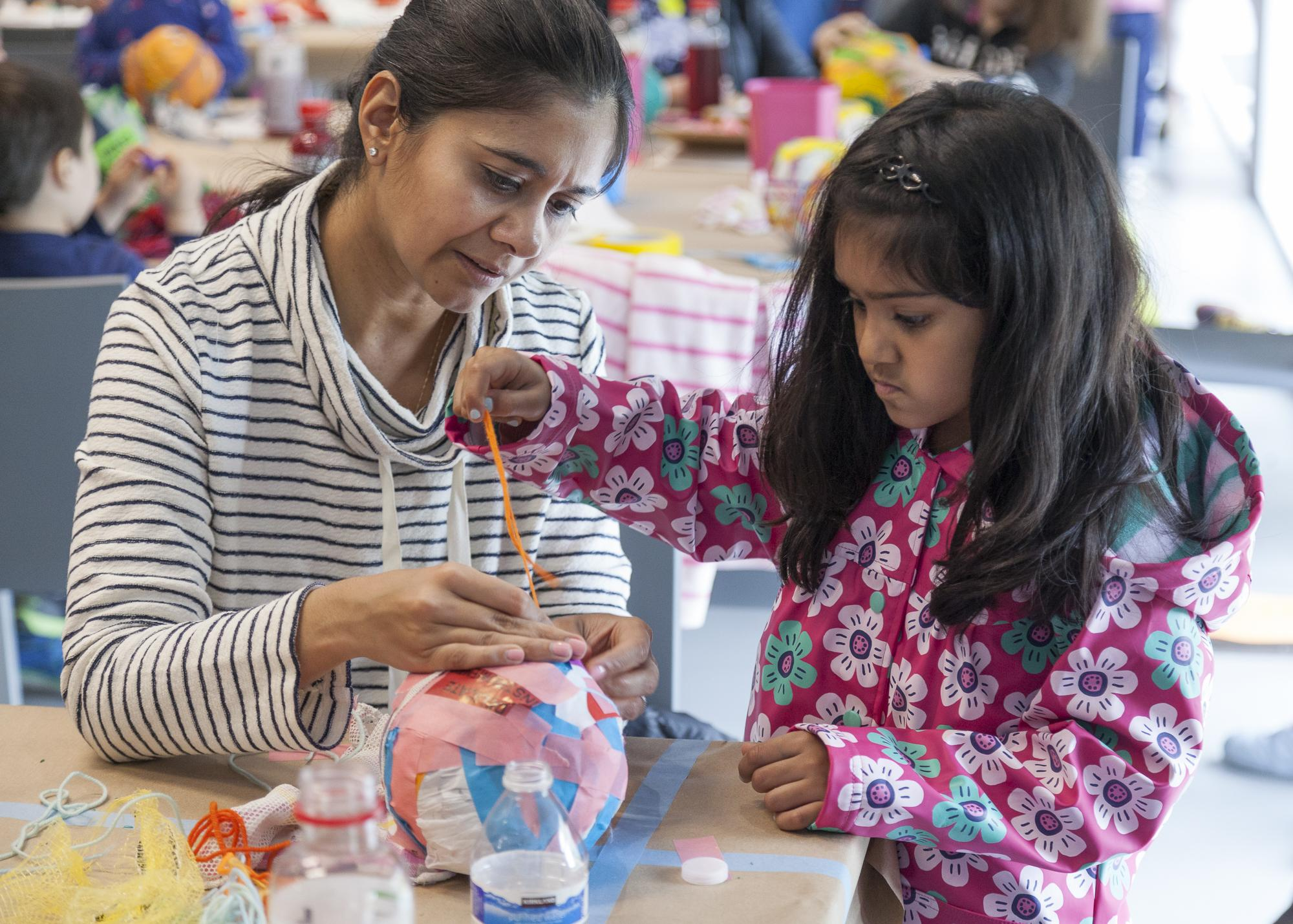 A child in a pink floral coat wraps an orange string around a colorful paper ball. An adult holds the string in place, assisting the child.