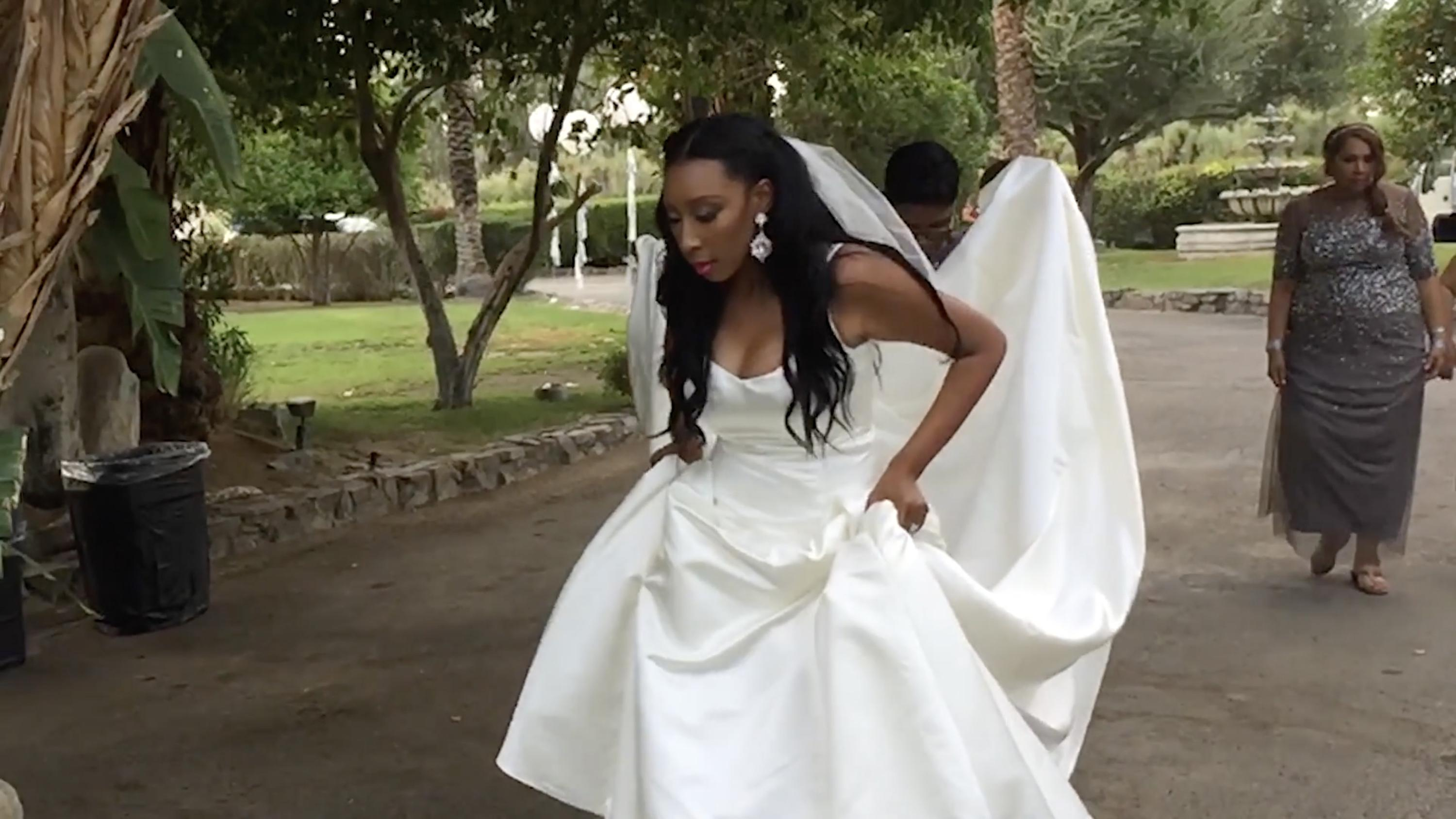A dark-skinned woman with her hair and makeup done wears a sleeveless wedding dress with a long train, held by another person behind her. She holds up the dress and looks down toward the path ahead of her.