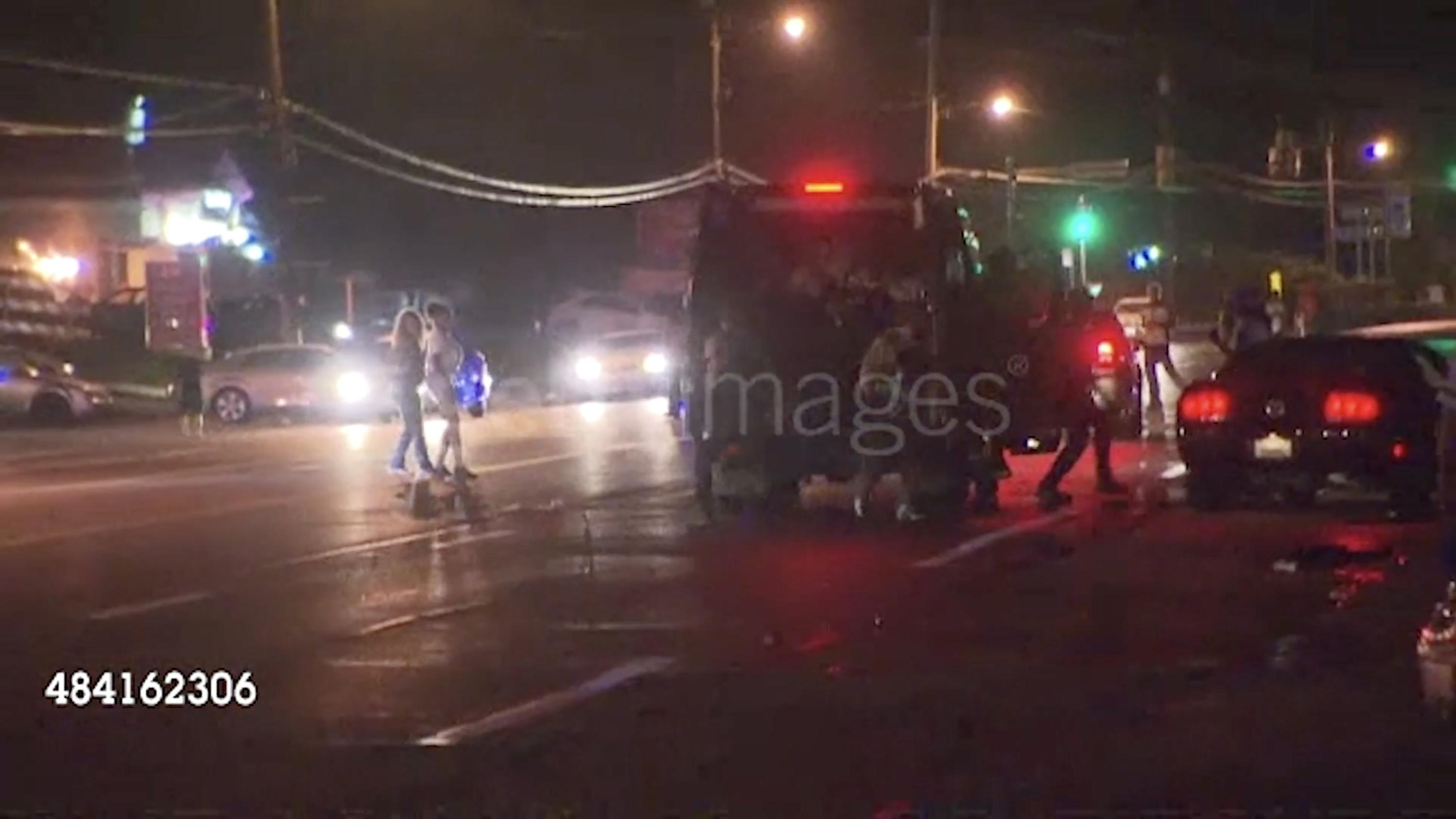 What appears to be a film still of a police or SWAT van on a street at night is watermarked with a Getty Images logo. People are walking on the street and emptying out the back of the van.