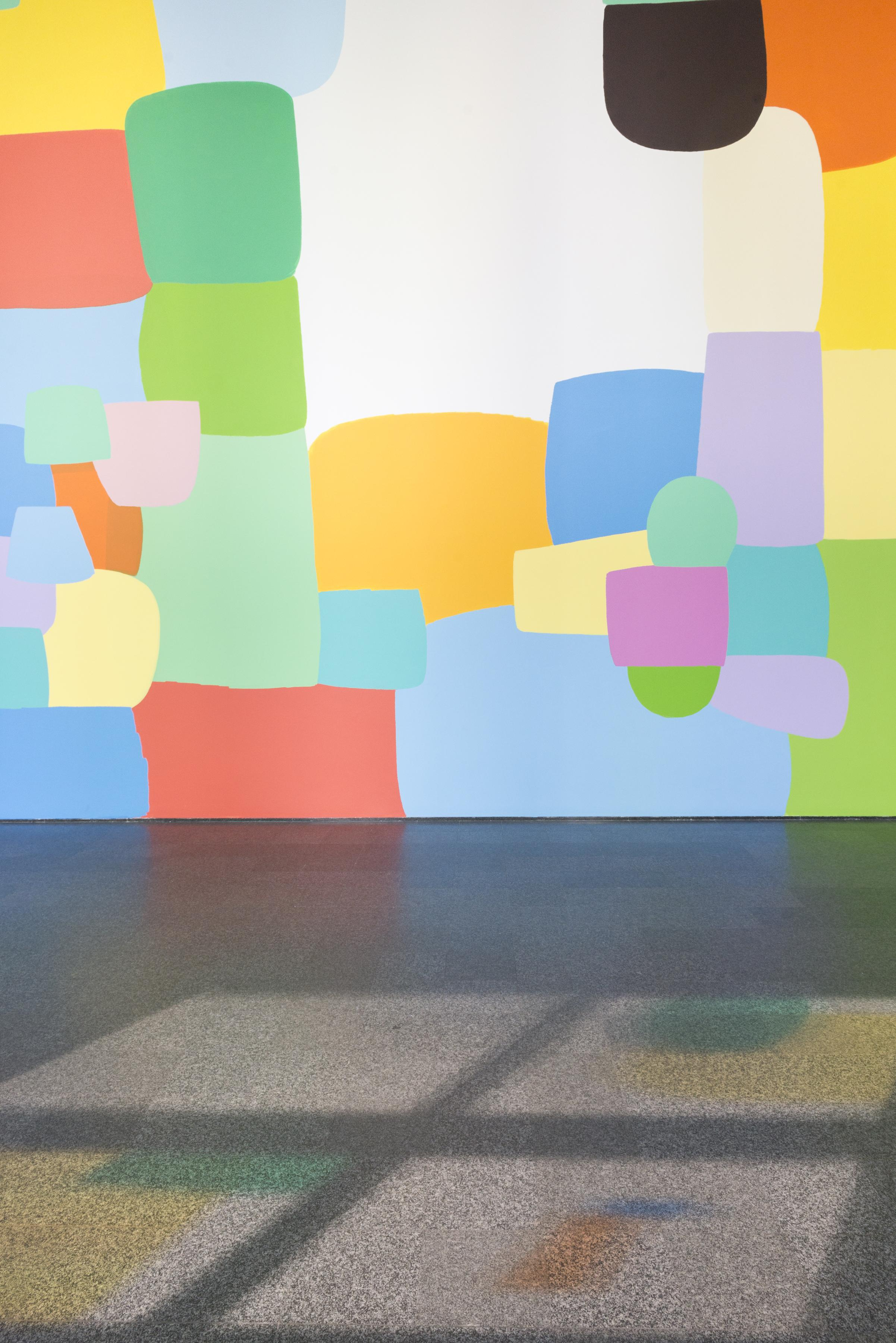 A large wall features a prominent, colorful mural. Light shining from windows casts colorful shadows on the floor.