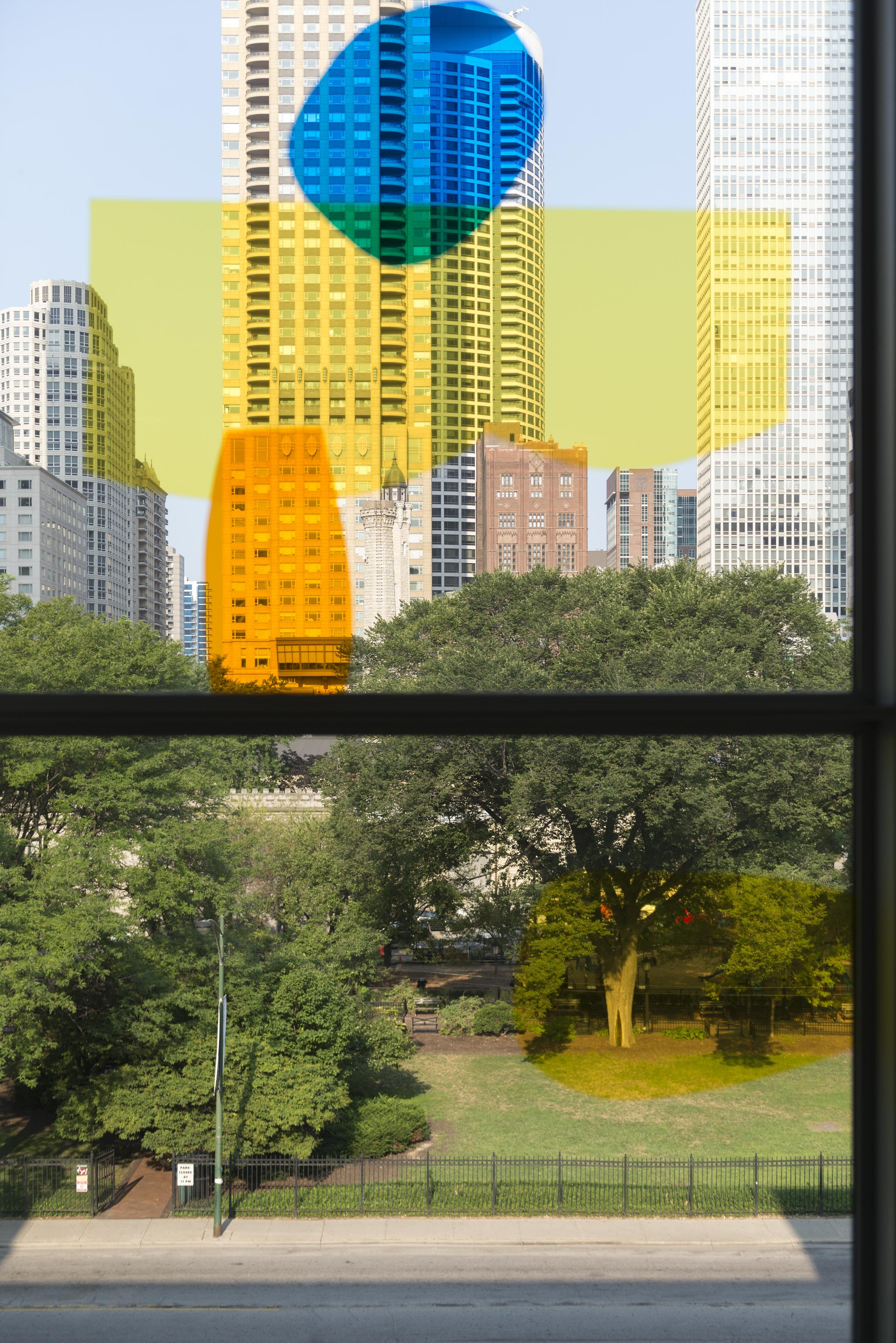 A window looking out on a park and the Chicago skyline has four brightly colored splotches of yellow, orange, and blue.