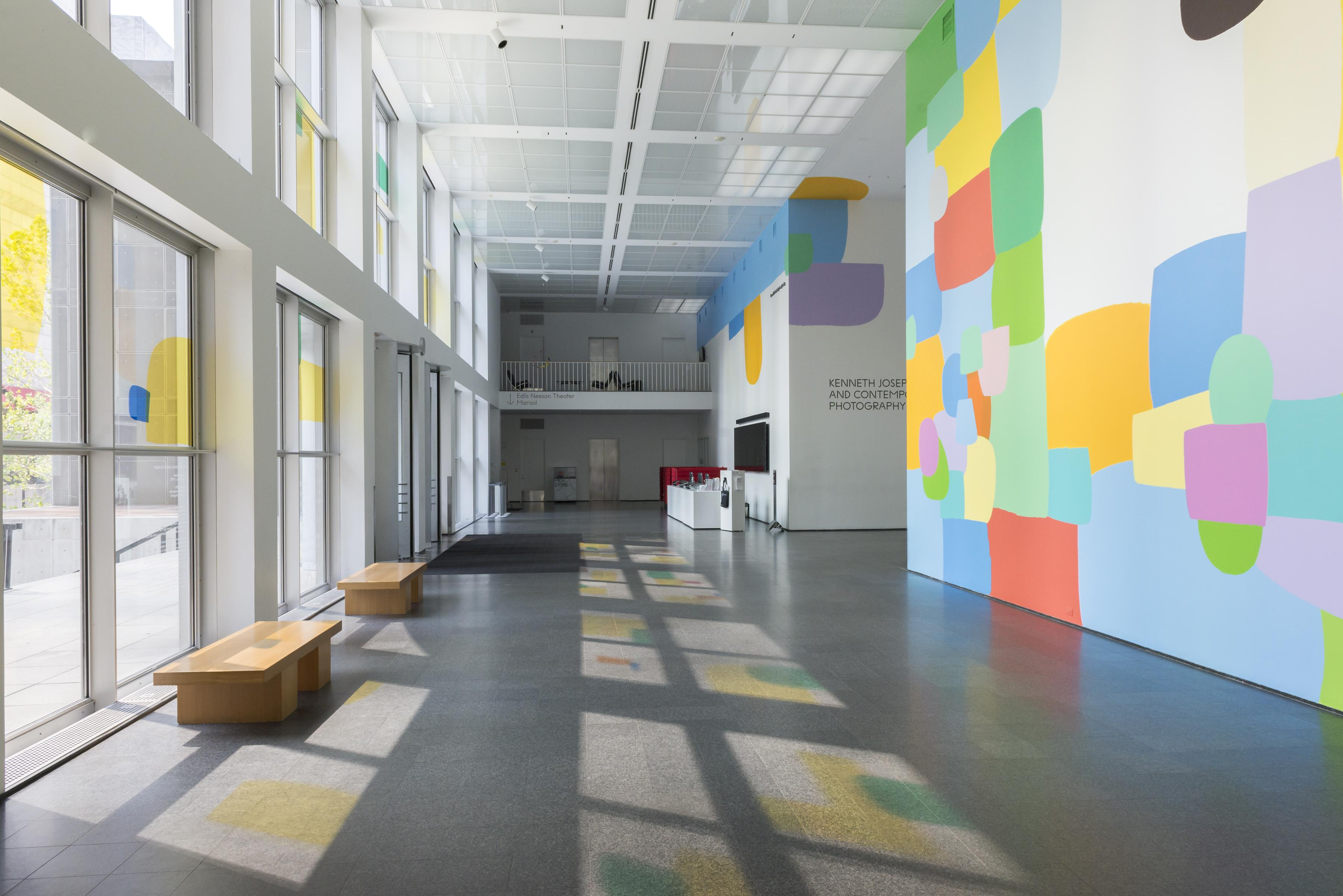 The MCA Atrium features a prominent, colorful mural on multiple walls. Colored panels on the windows create colorful shadows on the floor.