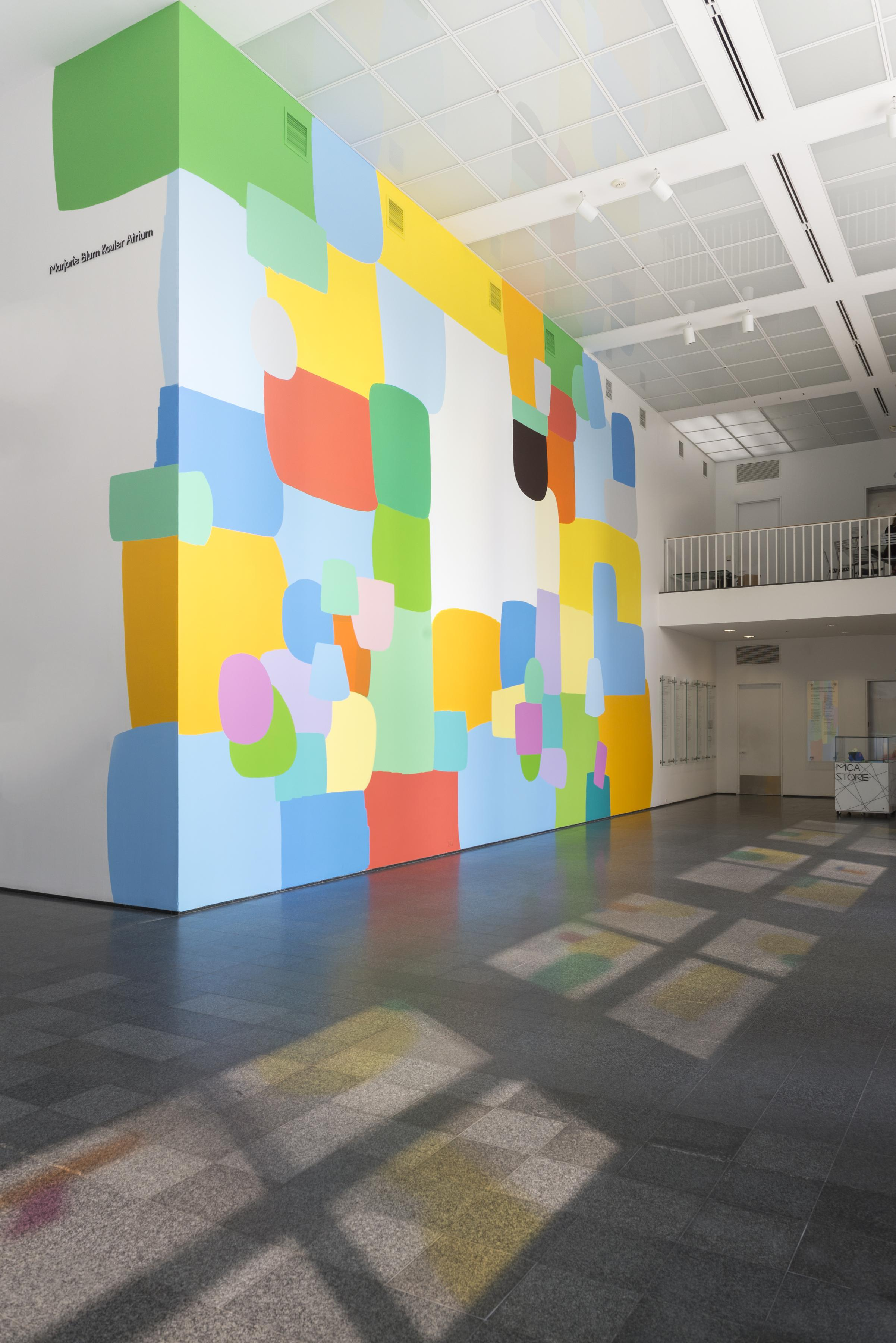 The MCA Atrium features a prominent, colorful mural on the walls and spots of illuminated color on the floor.