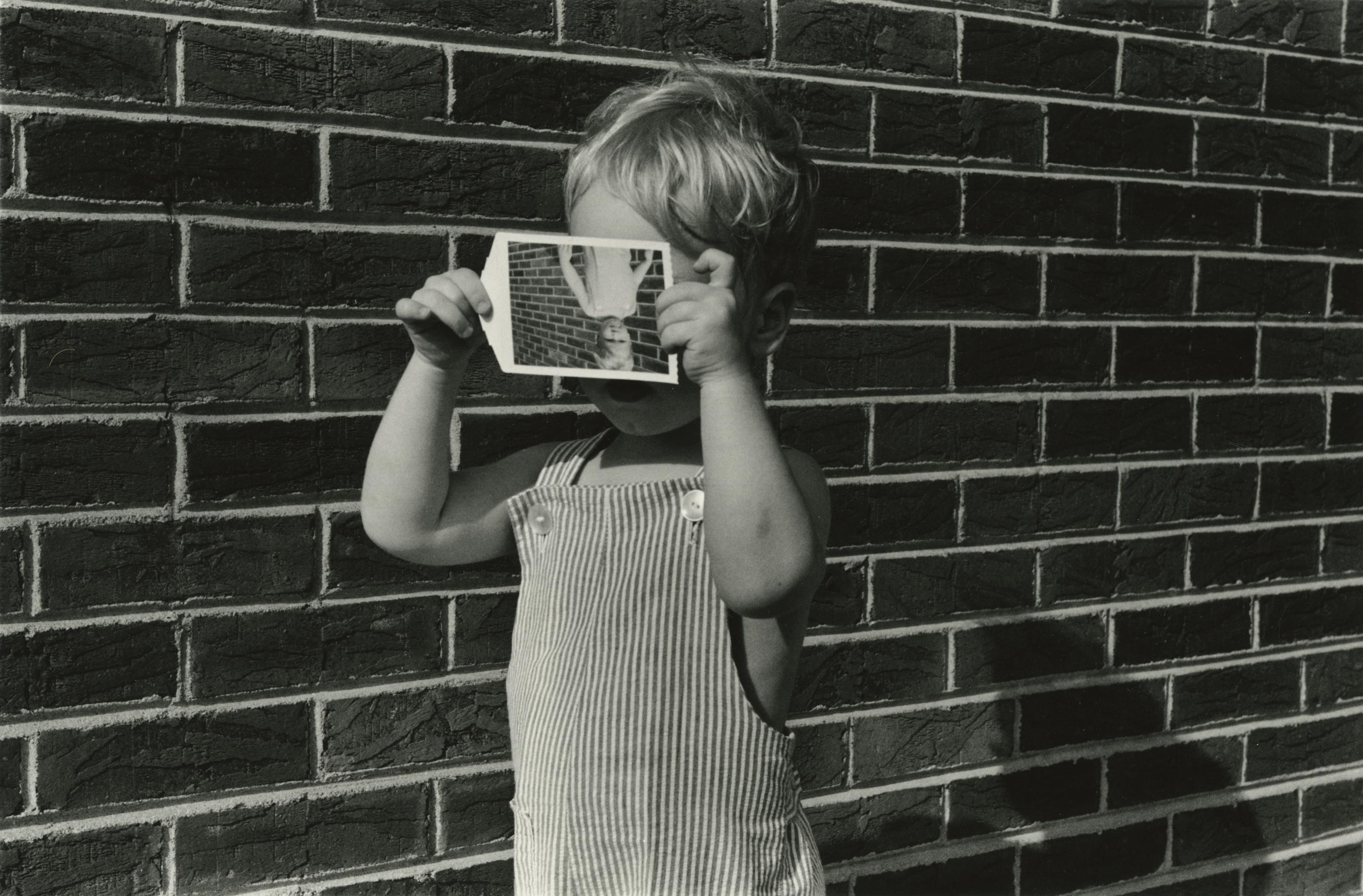 A child stands in front of a brick wall, holding in front of his face an upside-down snapshot of himself standing in front of a brick wall.