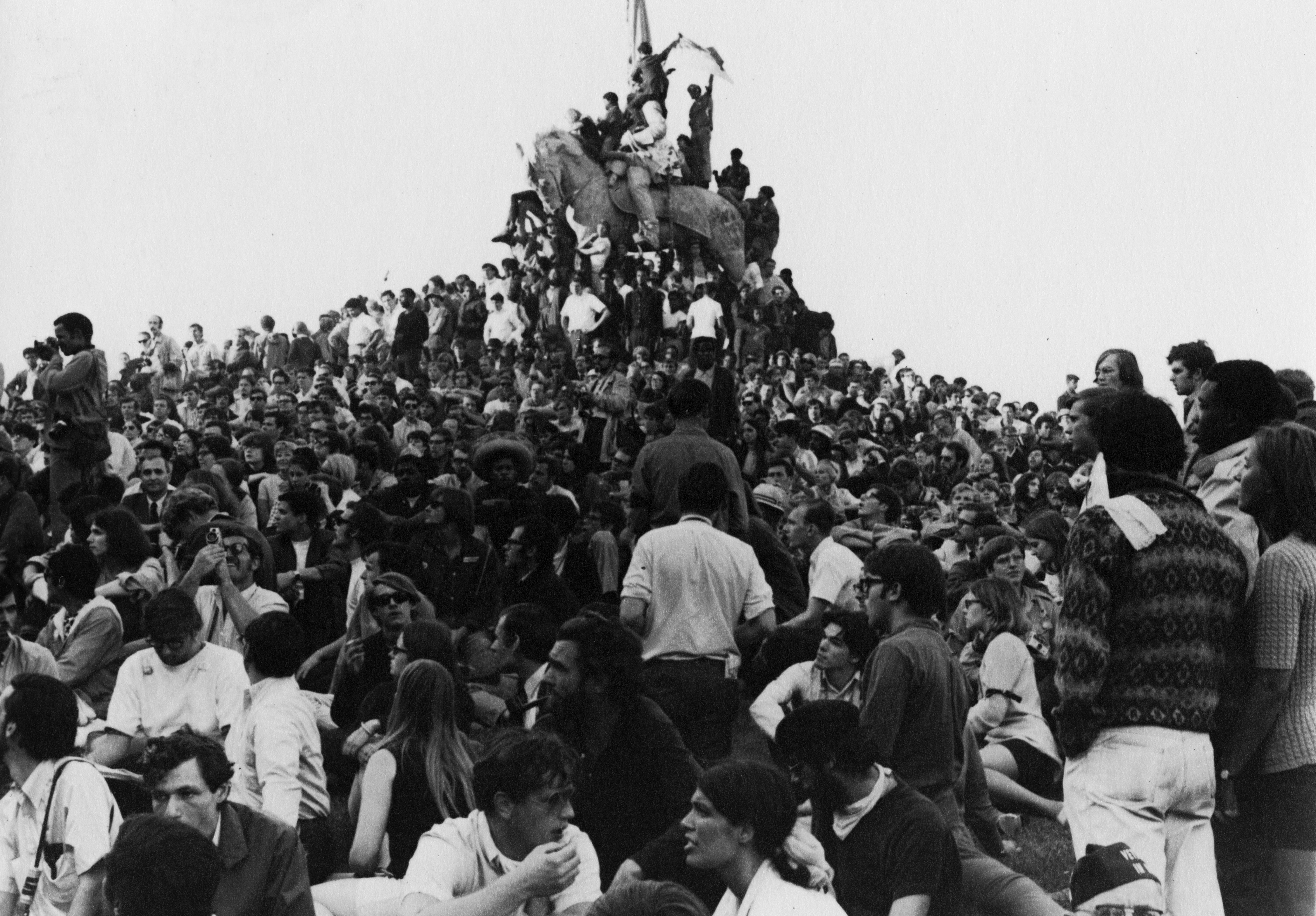 A black-and-white image shows a dense crowd of diverse young people gathered around and upon an elevated statue of a horse. Some people are climbing the horse, with the person at the top waving a flag.