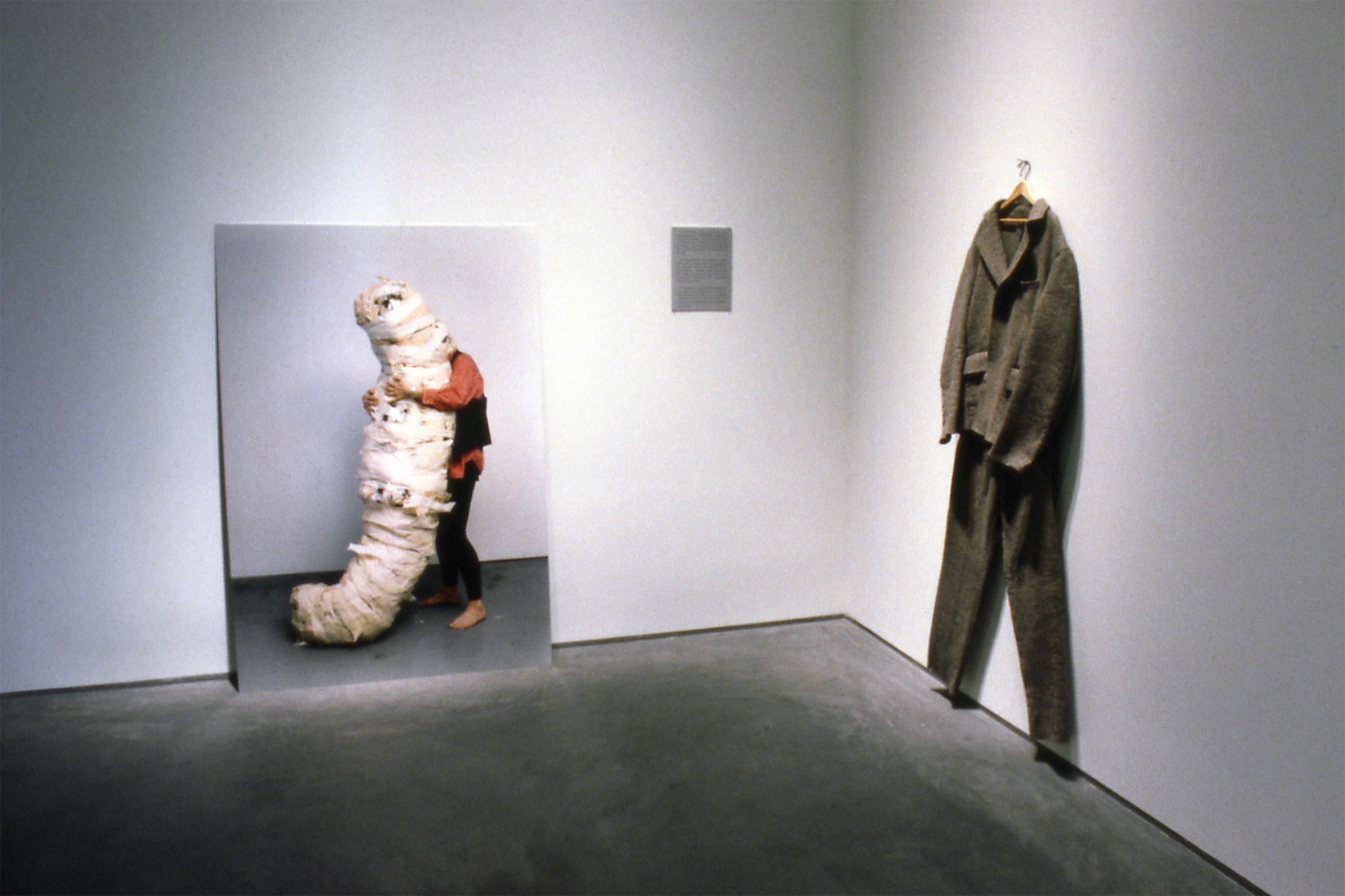 A gallery view of two works of art; one a large photo and other a suit on a hanger.
