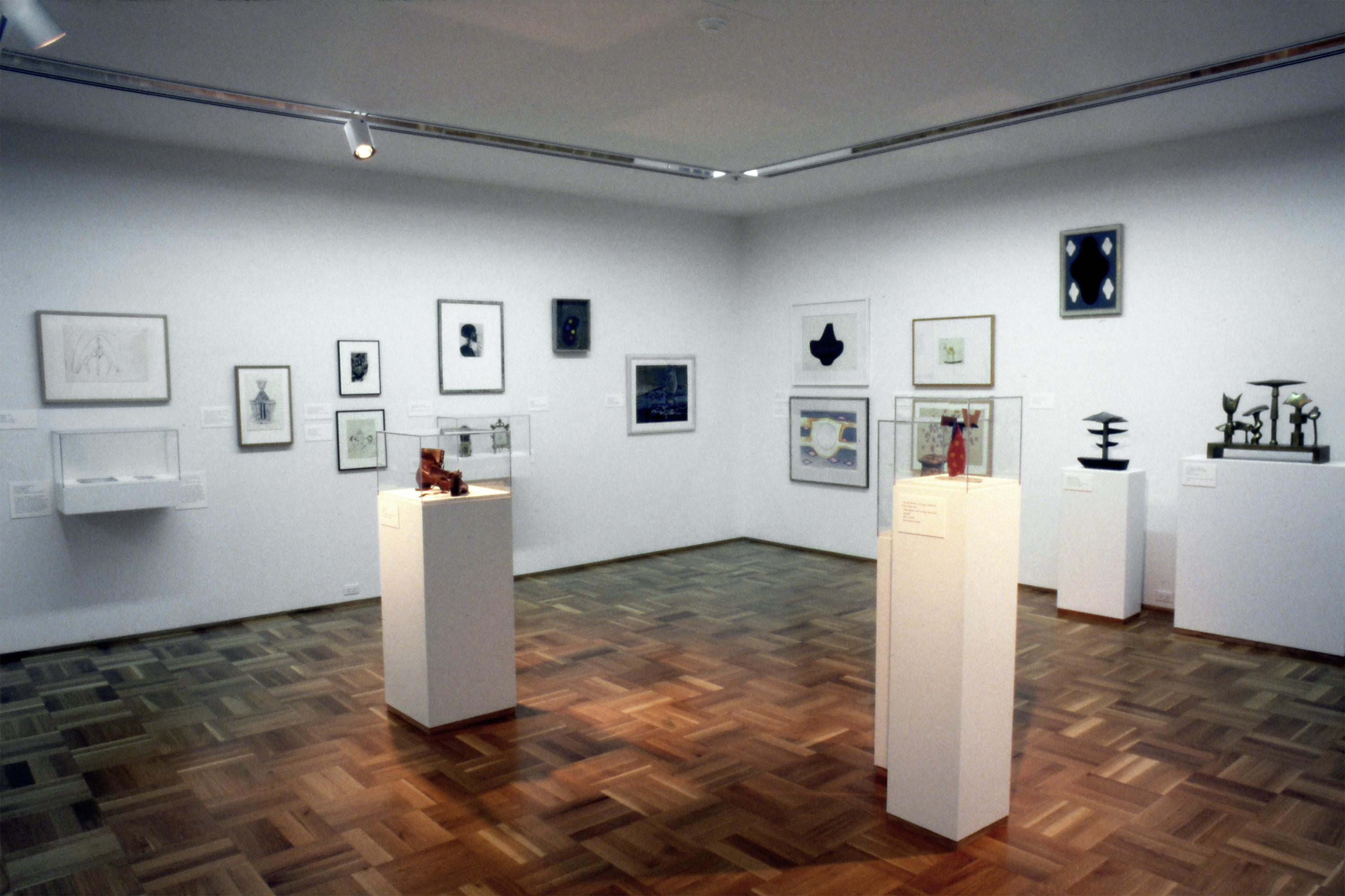 Gallery shot of sculptural artworks on pedestals and framed prints installed in white walled gallery with wooden floors.