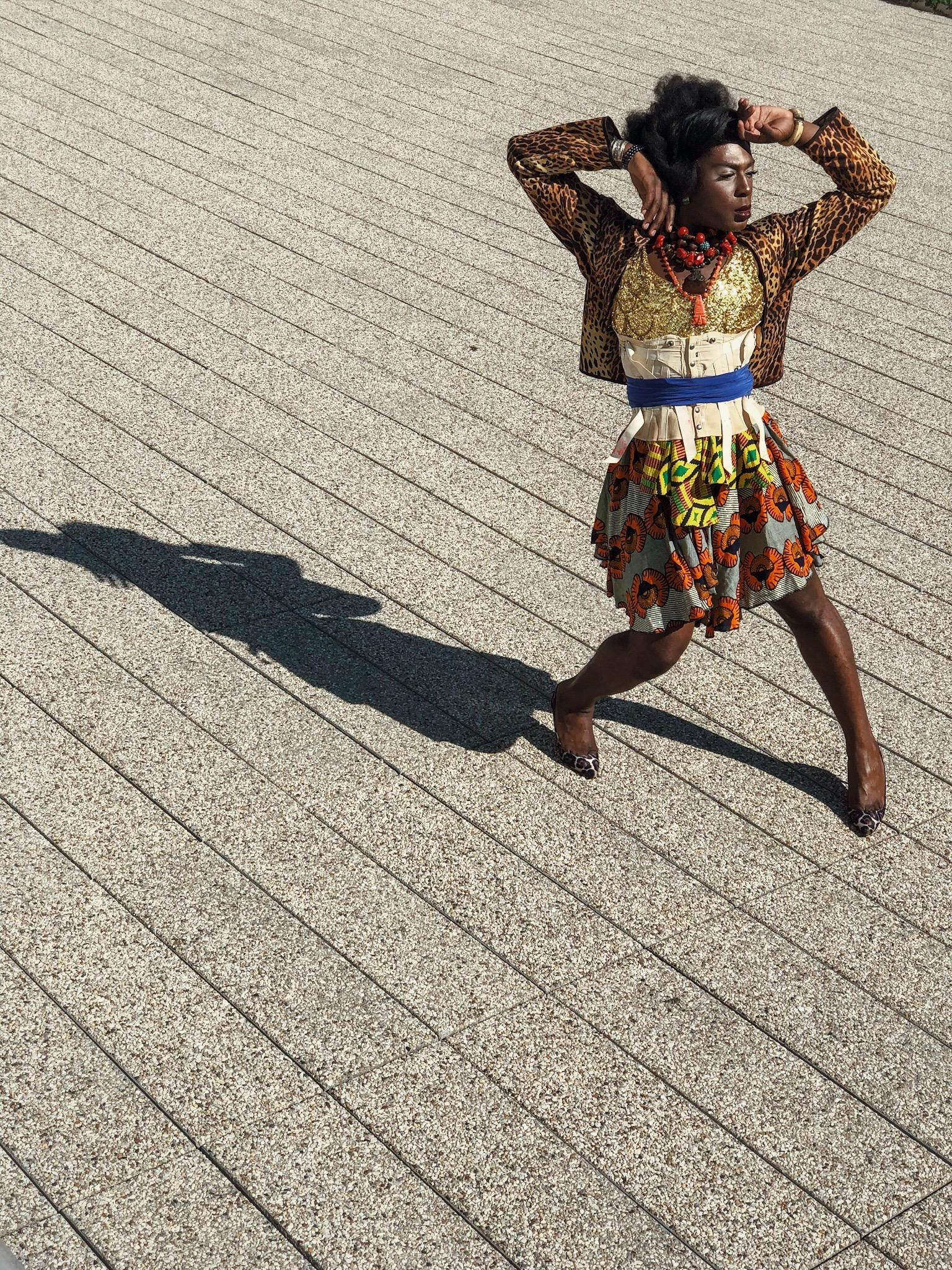 A dark complected person wearing a jacket, corset and many necklaces over an African print dress stands with splayed legs and upraised arms in a bright outdoor space.