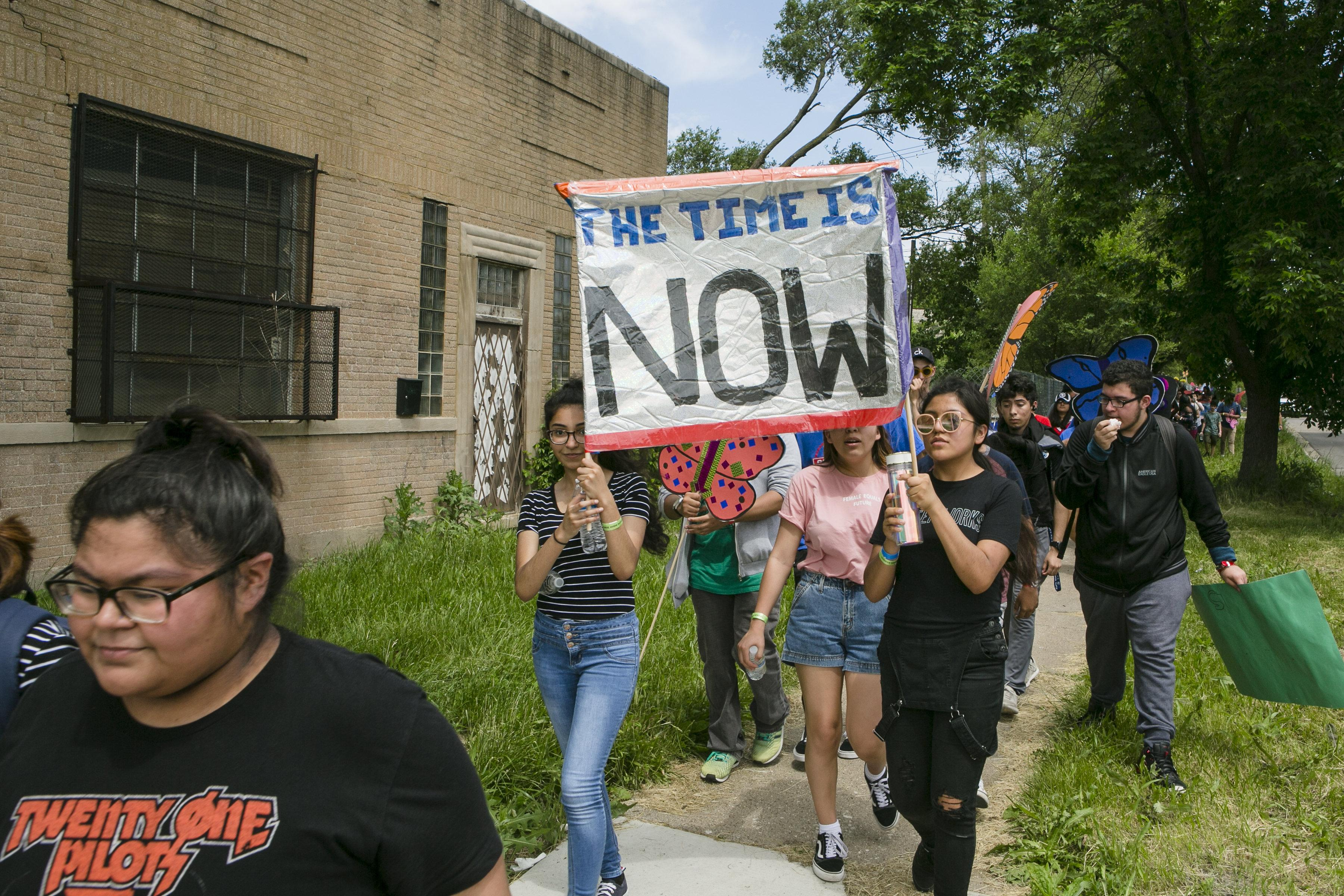 """A large group of young people march down a sidewalk with two people holding a prominent sign that reads """"The Time is Now."""""""