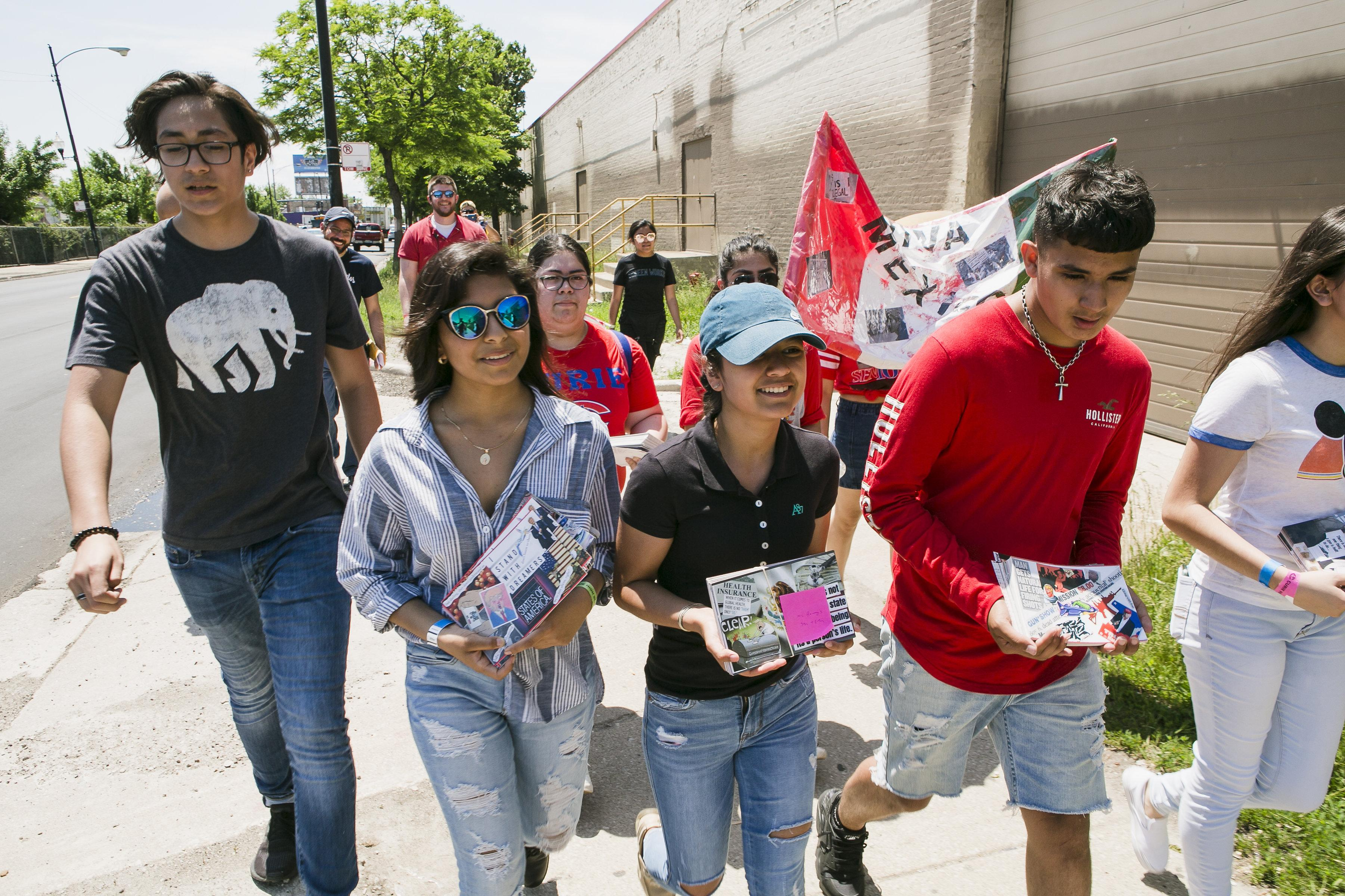 Nearly a dozen young people walking down a city sidewalk carry large postcards and a decorated flag of Mexico.