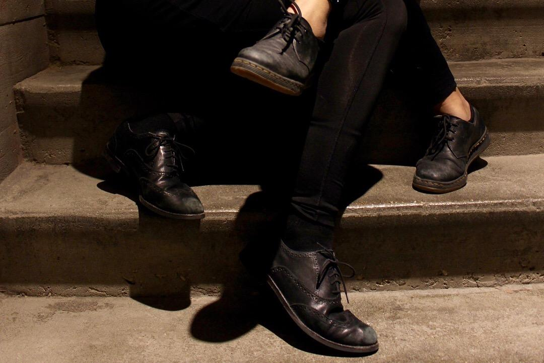 Two pairs of legs in black garments and black shoes are intertwined, seated on concrete steps