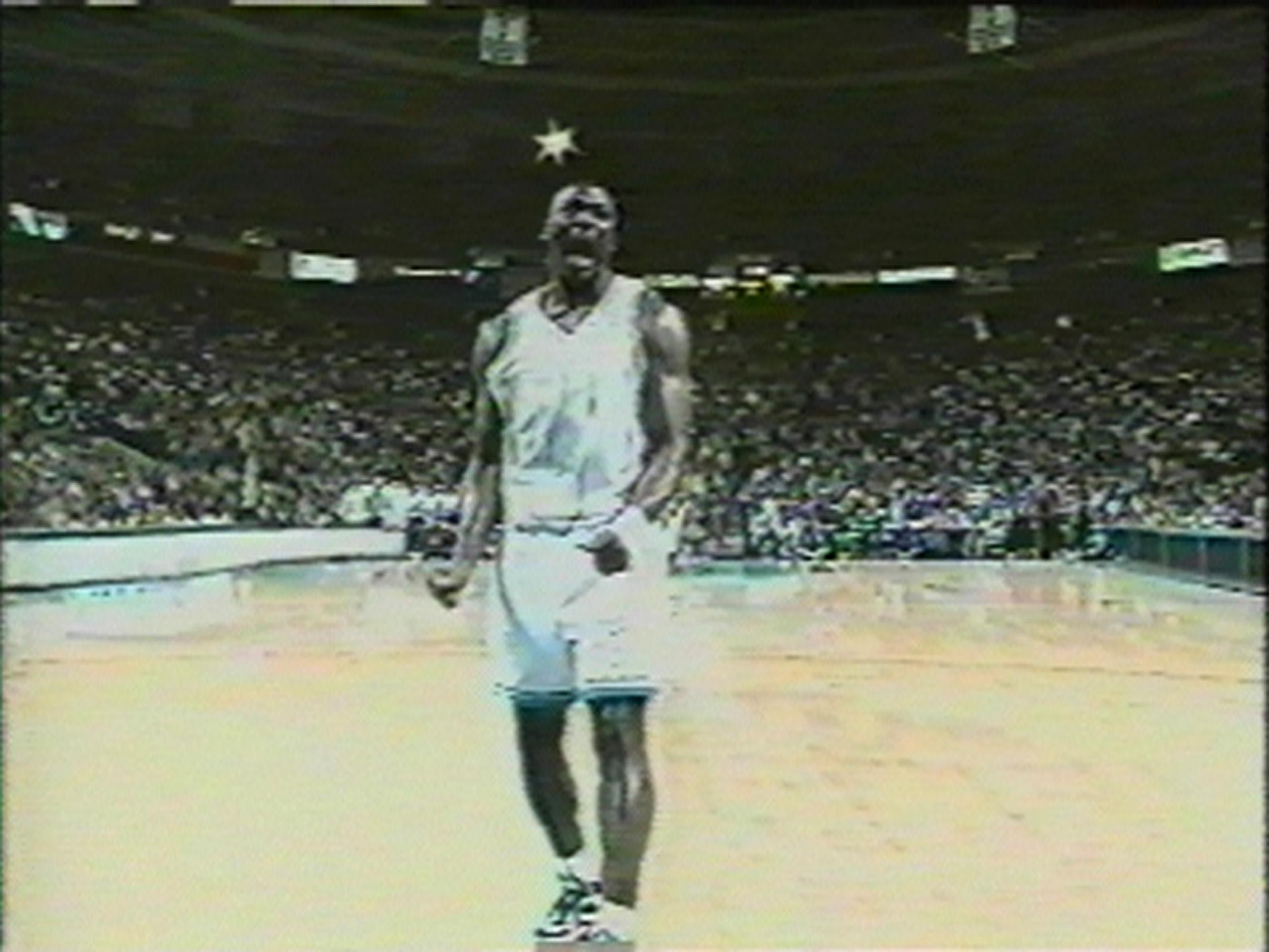 A dark-skinned basketball player wearing a light-blue uniform shouts in the middle of an empty basketball court.