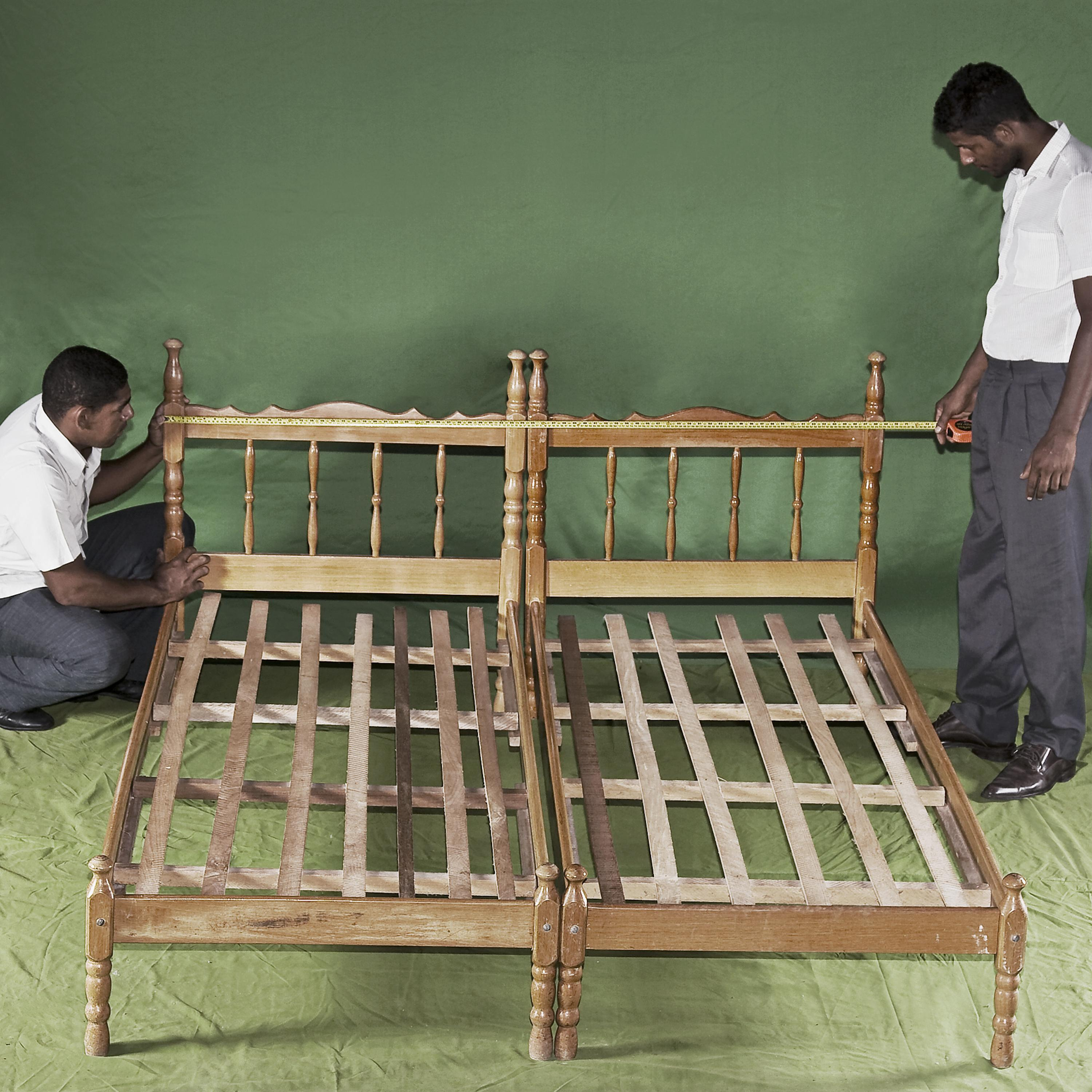 Two people wearing white shirts and black pants stand on opposite sides of a wooden bed frame in a green room.