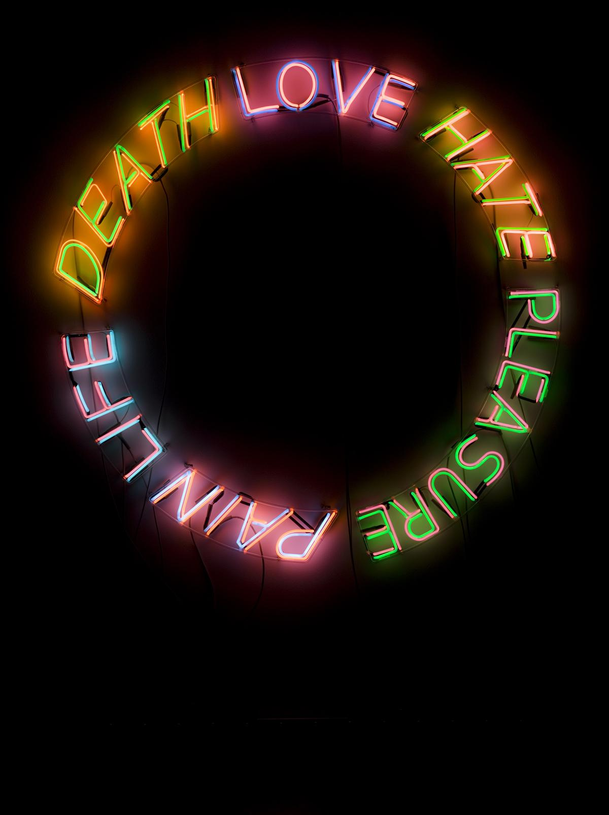 """The words """"DEATH,"""" """"LOVE,"""" """"HATE,"""" """"PLEASURE,"""" """"PAIN,"""" and """"LIFE"""" appear in illuminated neon, organized in a circle against a black background. In order, their colors are orange, purple, pink, green, and blue."""