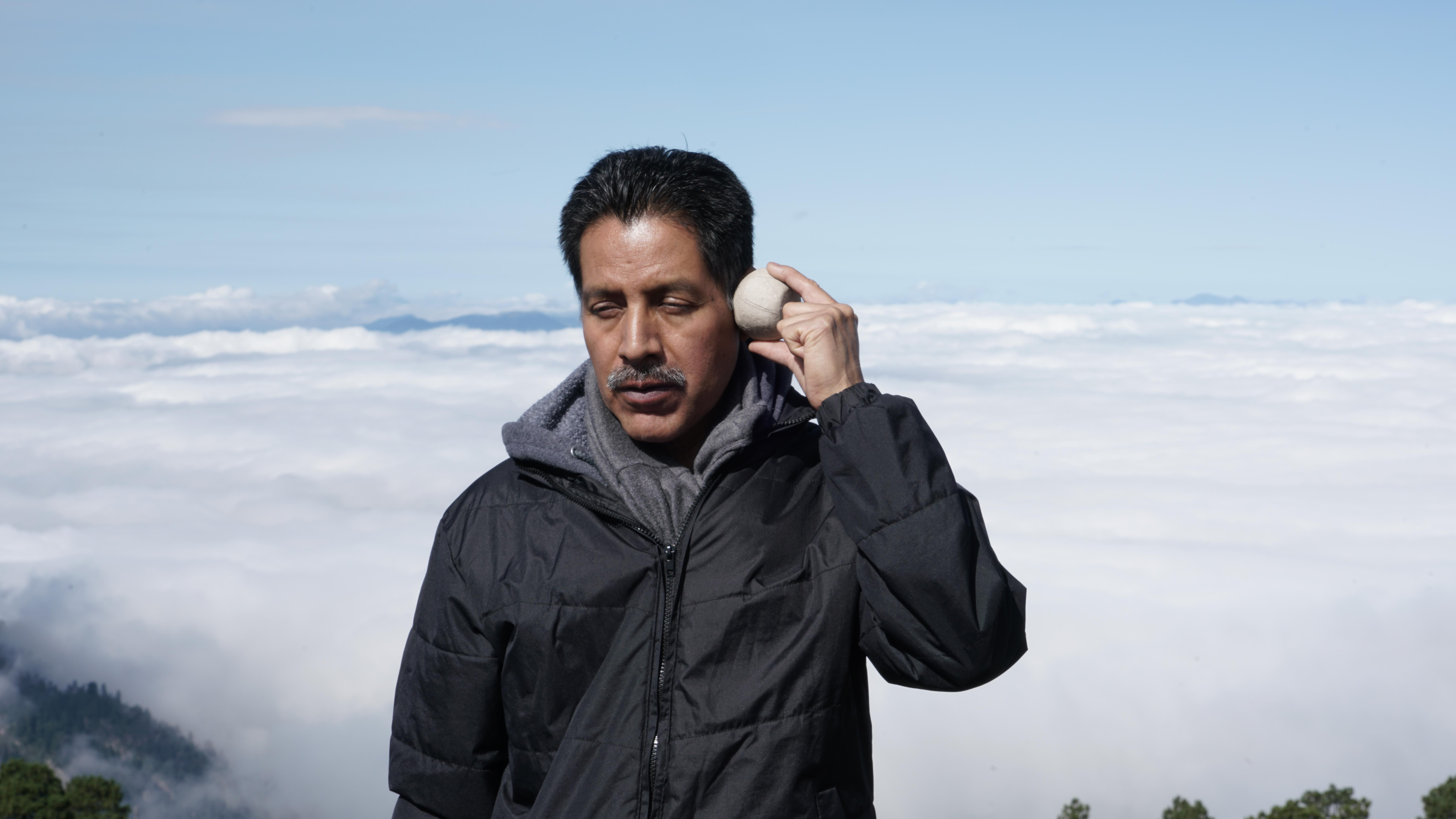 A man with medium-toned skin closes his eyes and holds a round, rock-like object against his temple. Behind him is a low cloud bank, indicating that he is standing at a very high elevation.