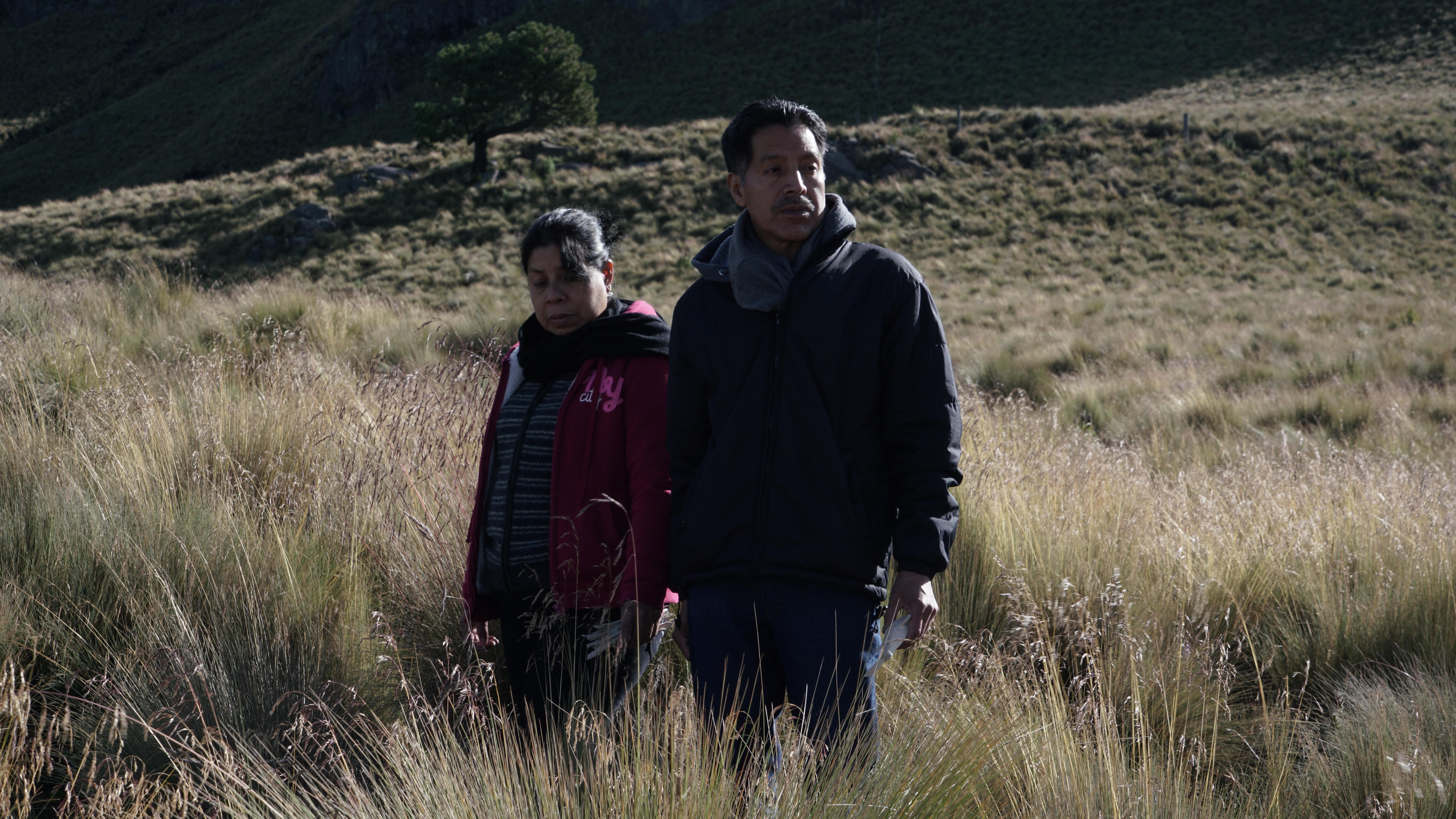 Two adults stand in an open field.