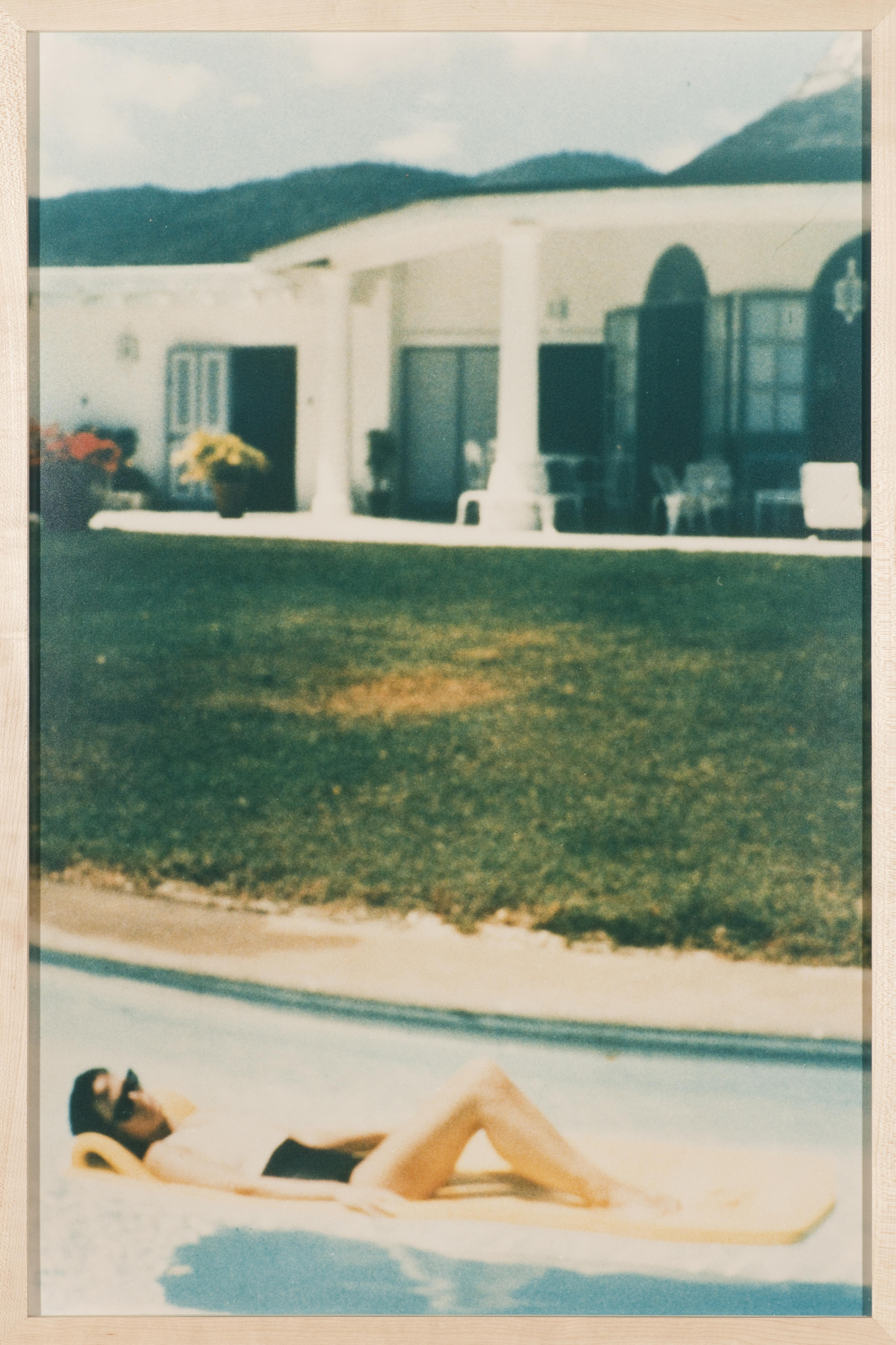 In what appears to be an aged photograph, a dark-haired person reclines on a lounge pool float in front of a large yard and house.