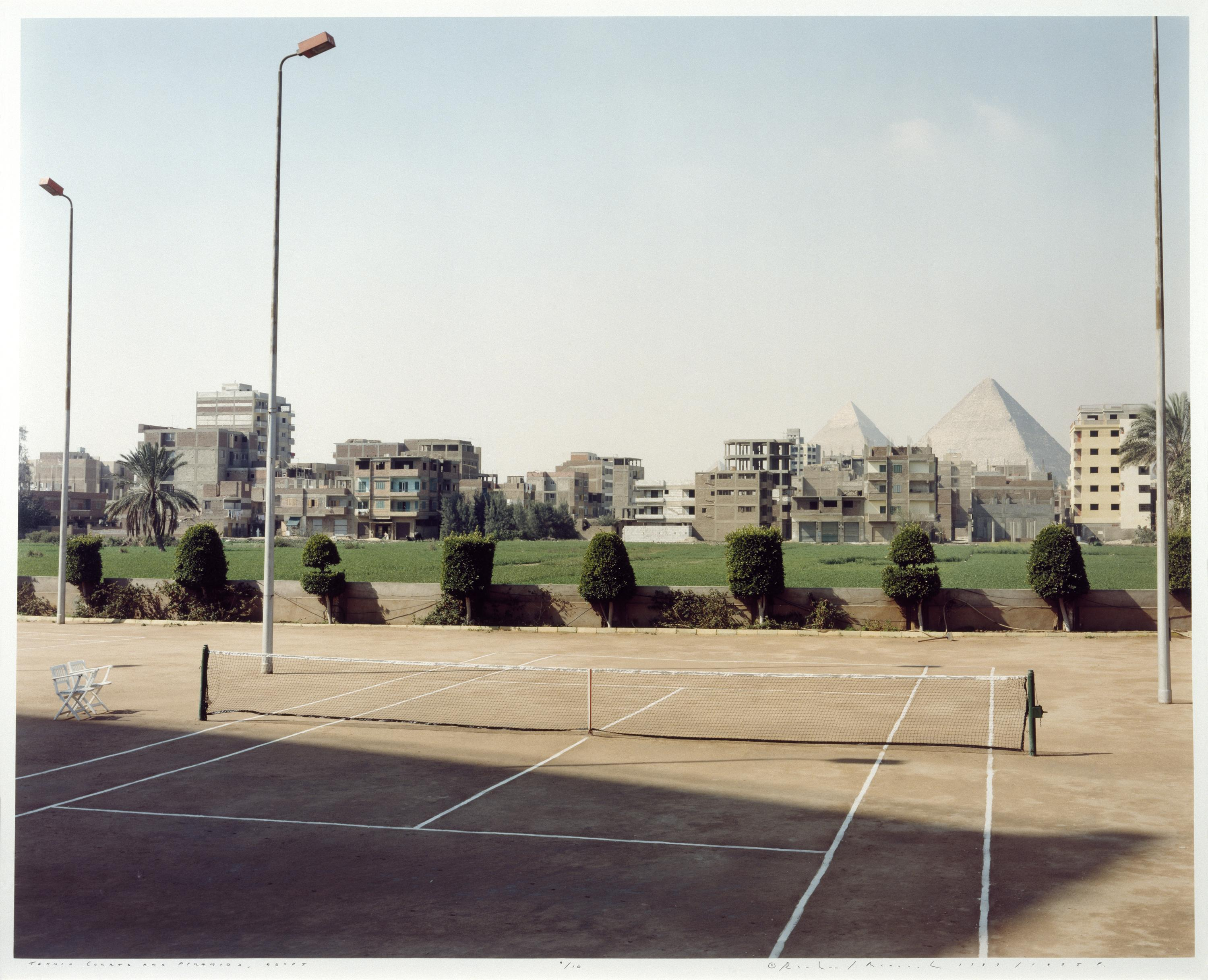 In a complex but quiet scene, a tennis court occupies the foreground. Behind the court are a line of modernist buildings, with the Egyptian pyramids looming in the distance.