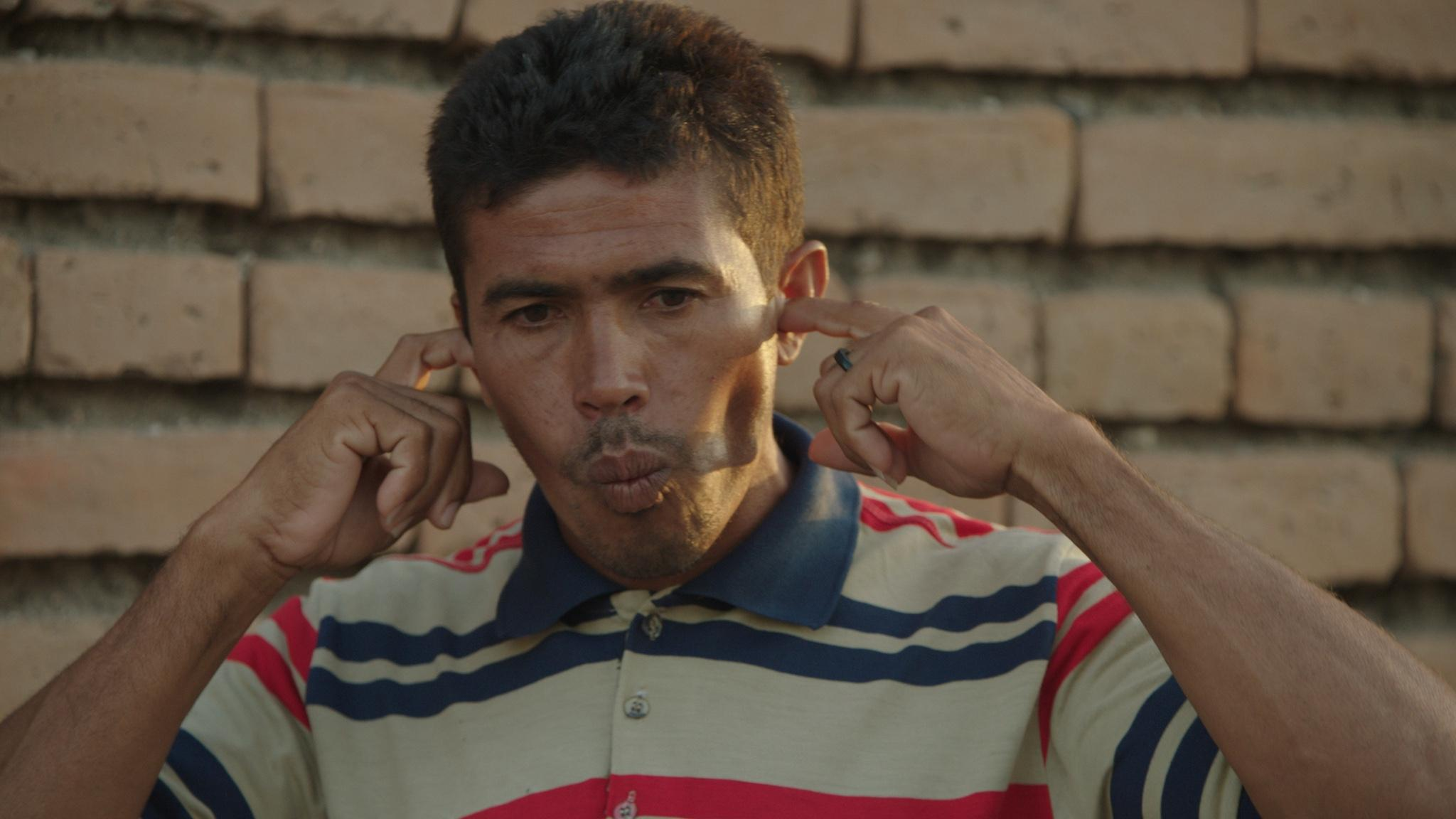A man wearing a striped polo shirt purses his lips while placing his index fingers in each ear.