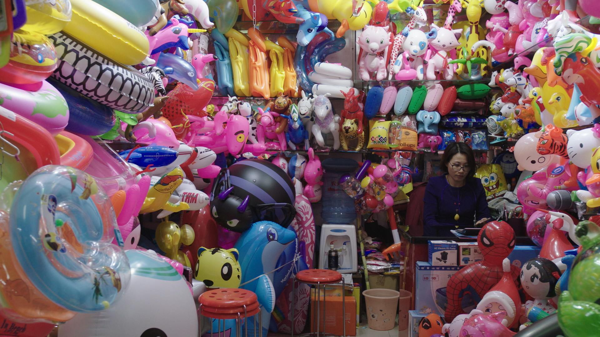 A woman sits in a room with walls fully covered with colorful inflatable animals and cartoon characters.
