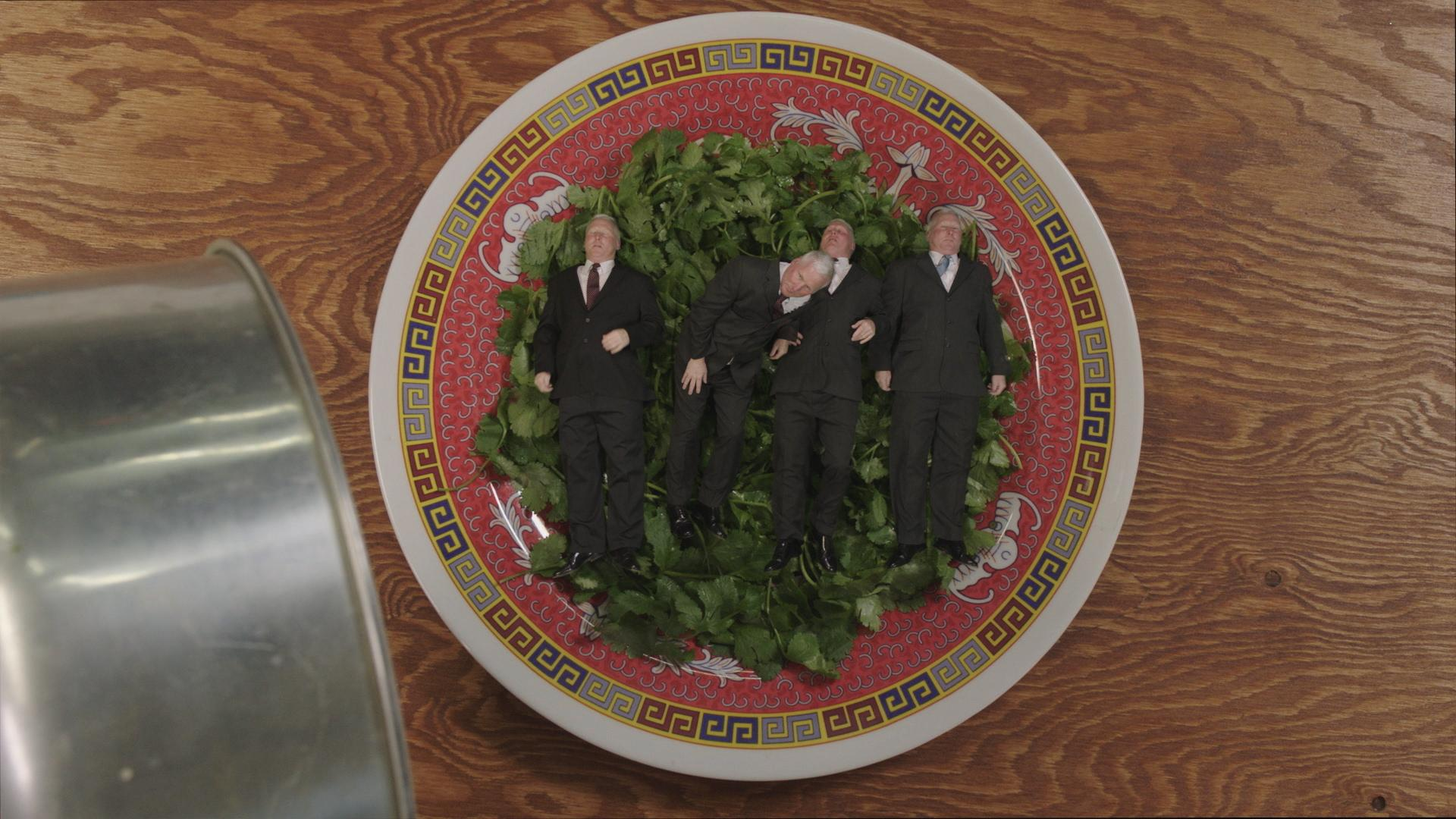 An ornately decorated plate holds a hearty serving of green herbs. Atop the herbs, four gray-haired men in suits lay side-by-side.