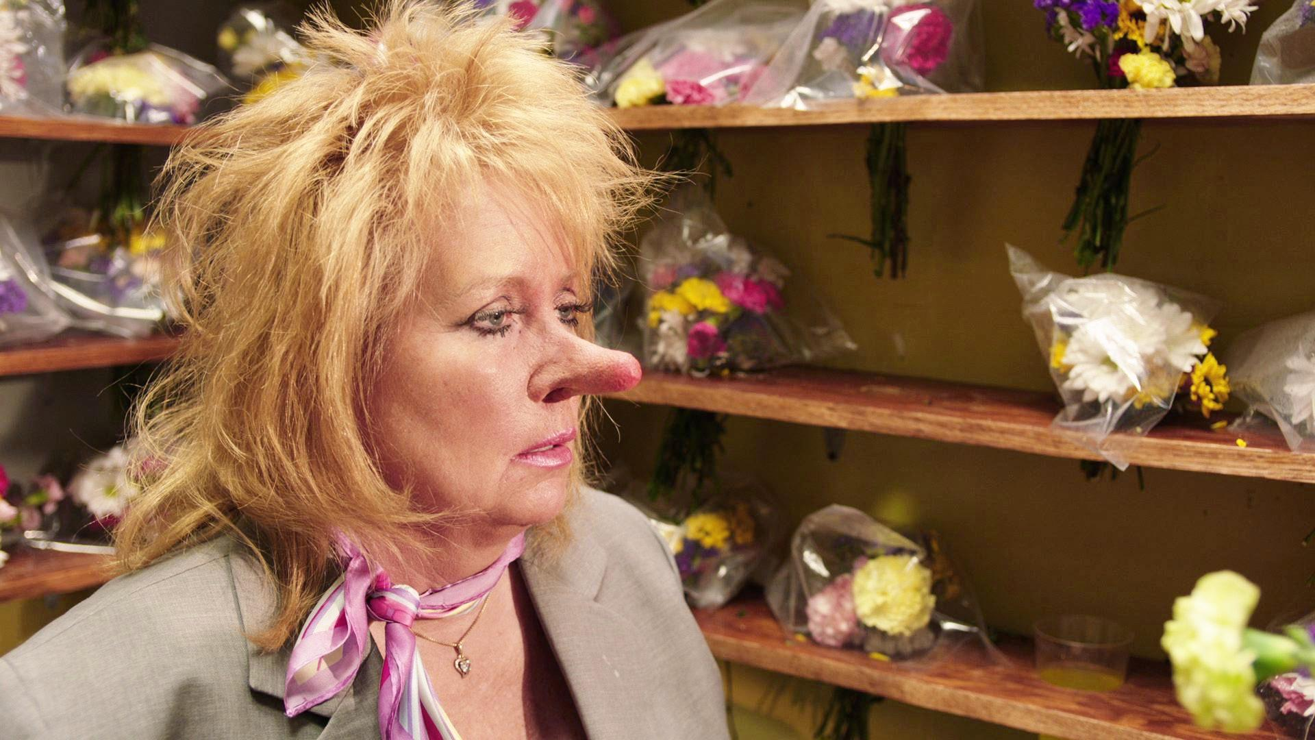 A woman with disheveled blonde hair and a comically long, pink-tipped nose is seen in front of wooden shelves of flower bouquets.