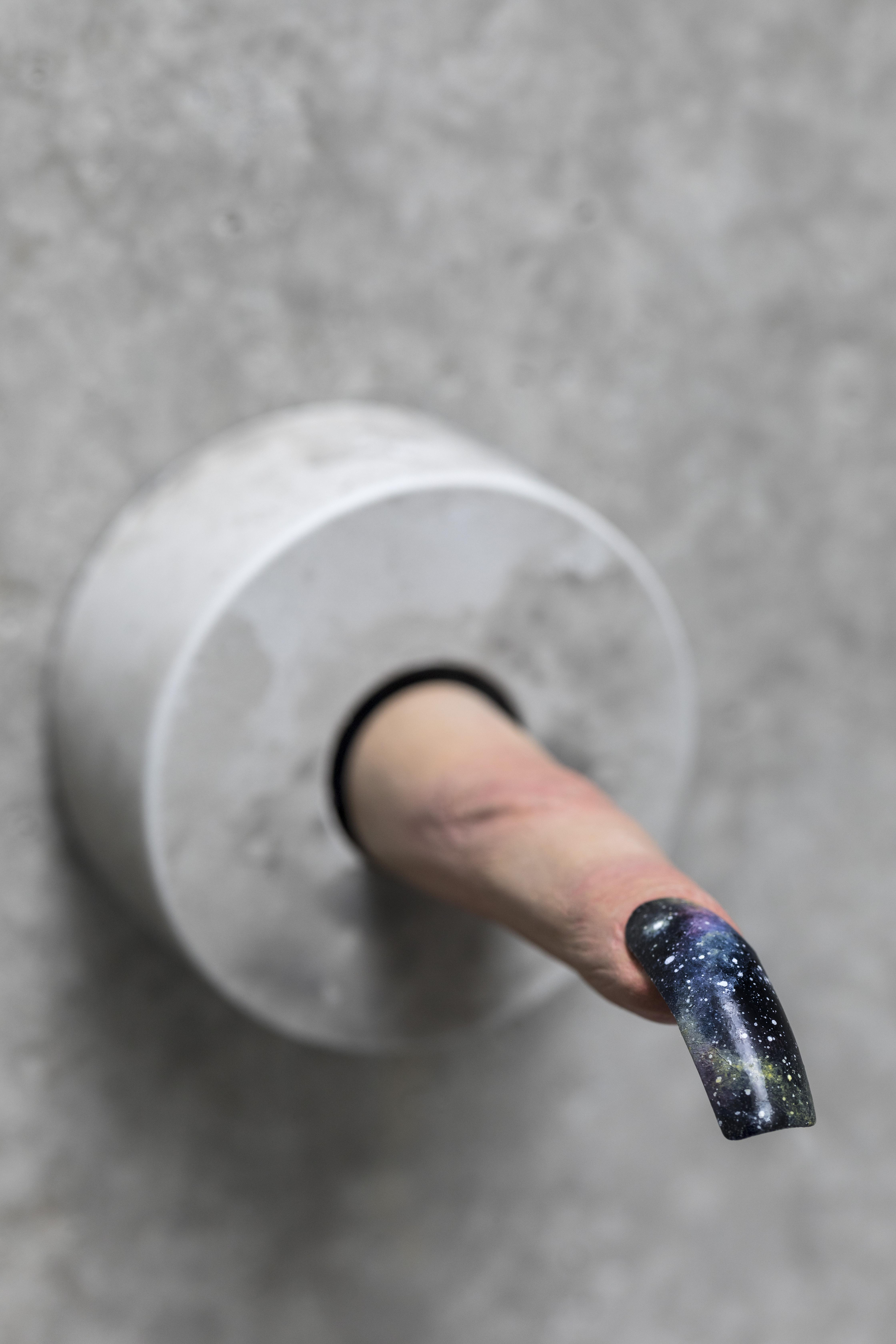 A light-skinned finger ending in a long fingernail extends out from a gray wall. The fingernail is painted black, with details similar to a night sky or galaxy.