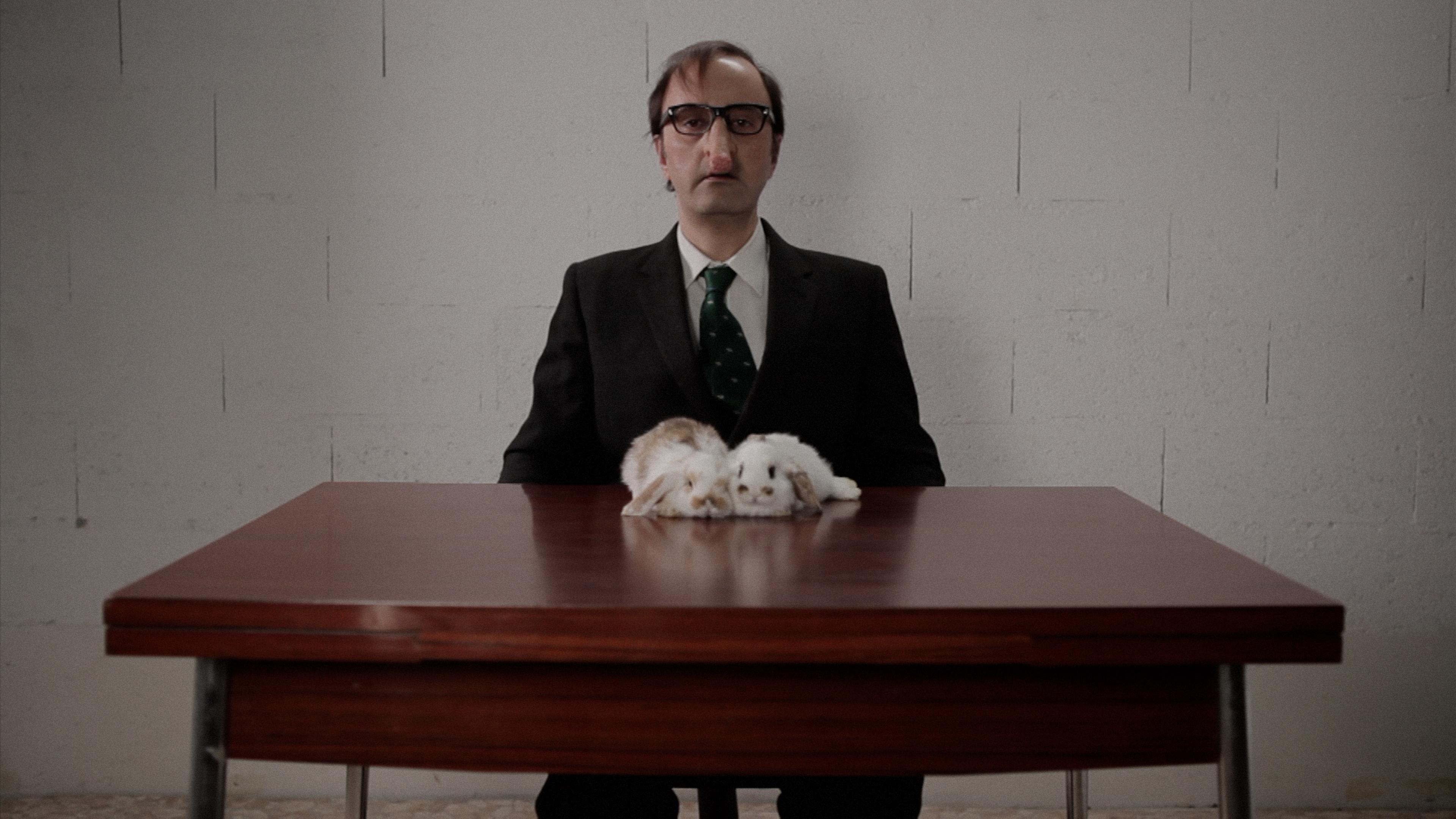 A balding man with thick-framed glasses and a strangely long nose looks directly at you. He sits at a table, upon which two white-and-brown rabbits are resting.