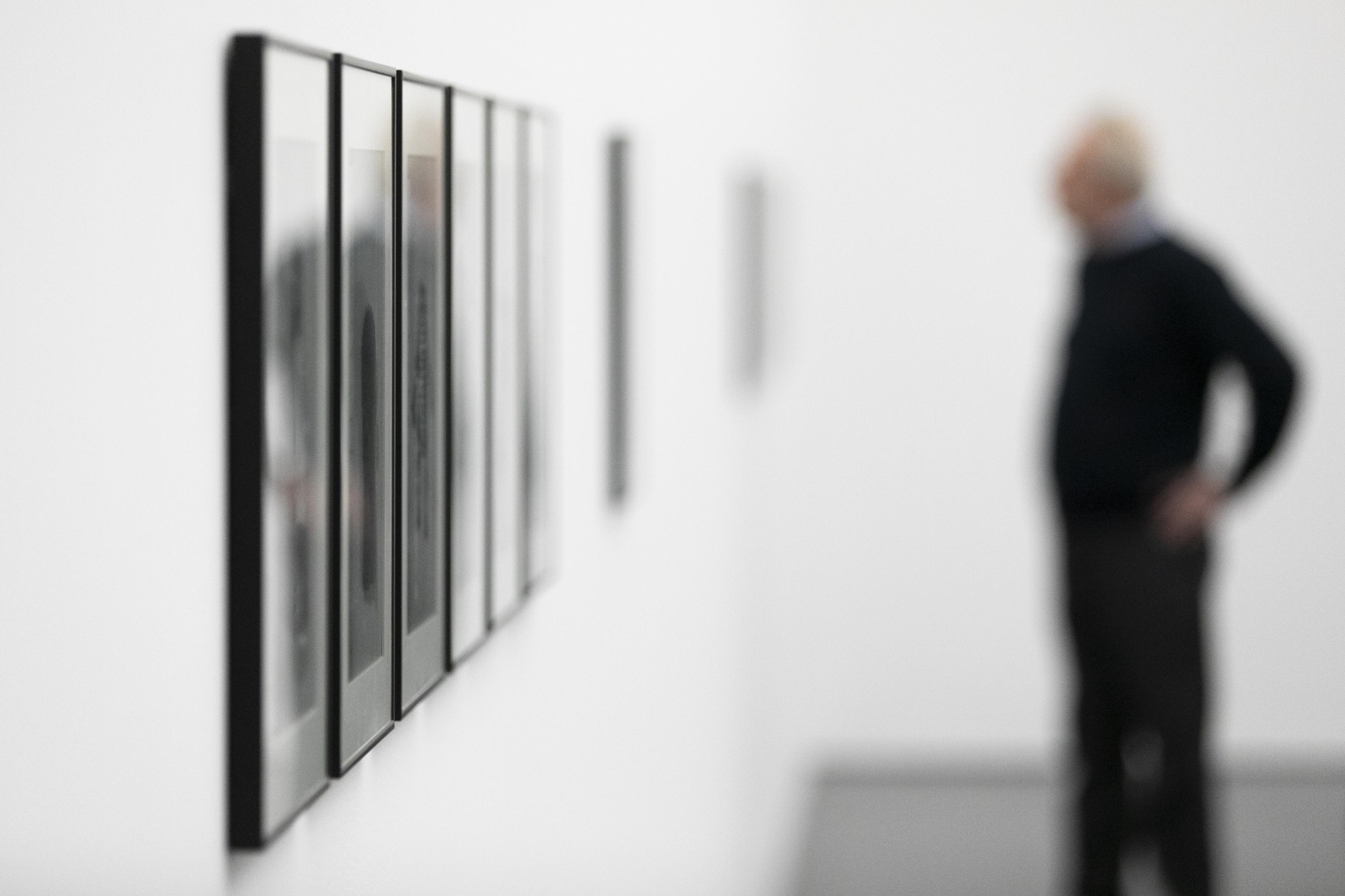 A blurred photo of a man looking at a gallery