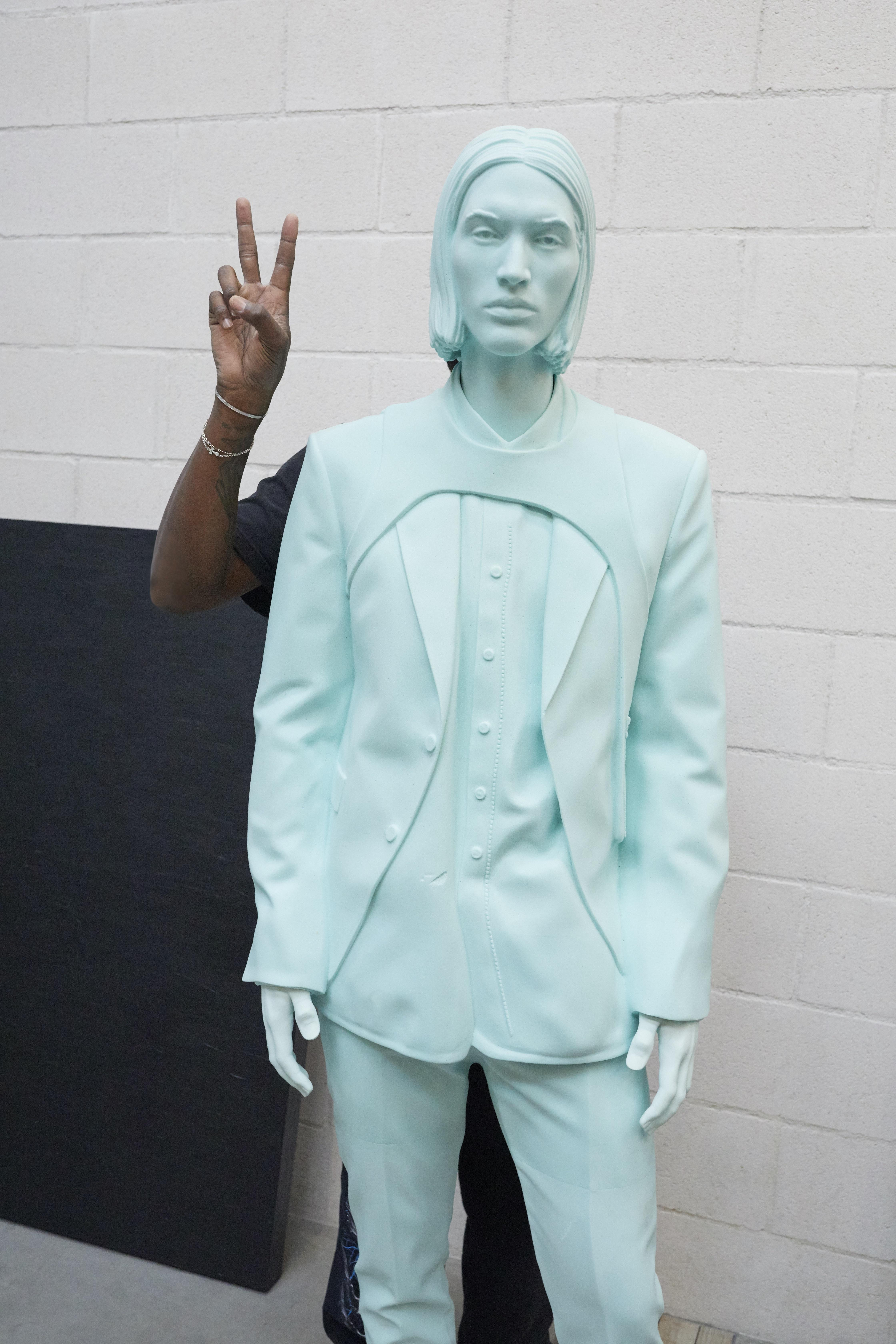 A dark-skinned arm holds up two fingers in a peace symbol from behind a monochrome light-blue mannequin.