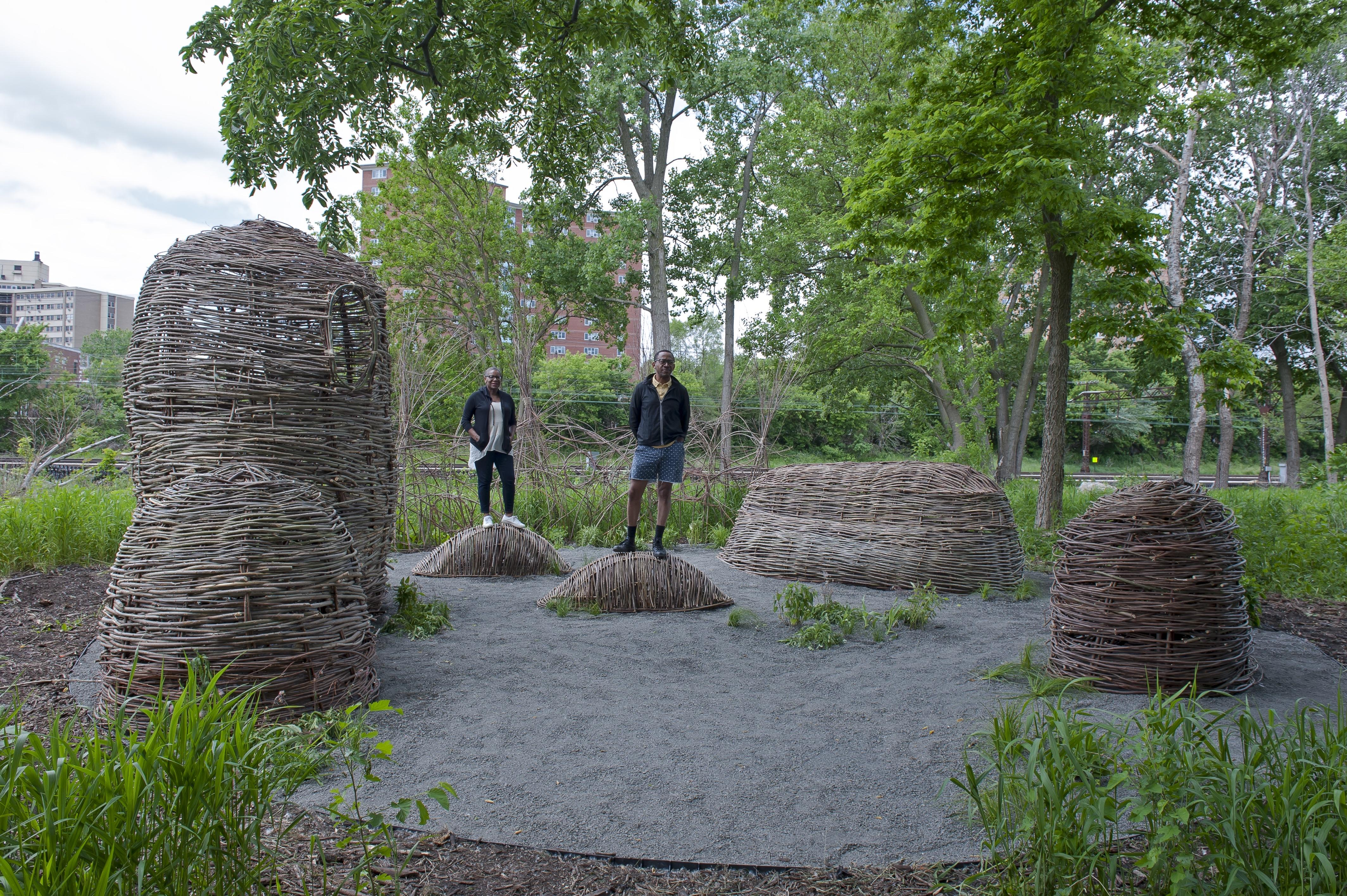 Two people stand on small mounds that are woven like wicker baskets. They are surrounded by four other similar mounds and urban greenery.