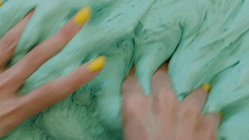 In a short animation, light-skinned hands with vivid yellow finger nails repeatedly massage a large mass of mint-green goo.