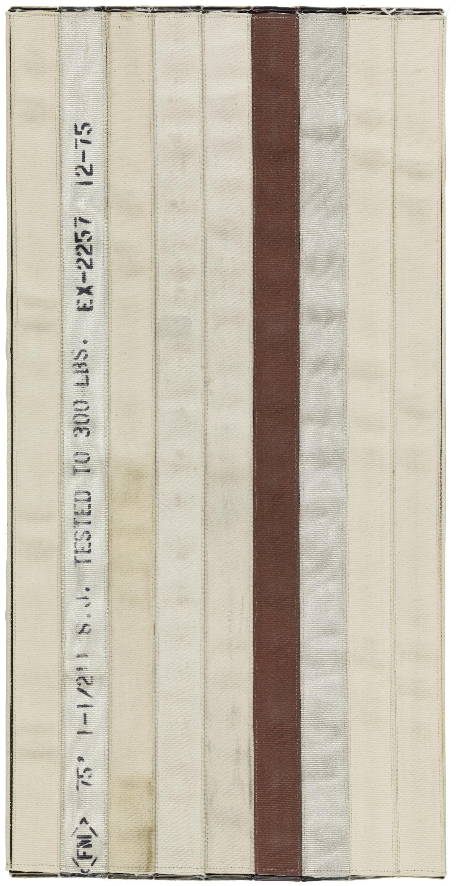 """A vertically oriented artwork appears to consist of seatbelt-like strips of fabric stitched together. One strip shows black text including """"TESTED TO 300 LBS."""""""