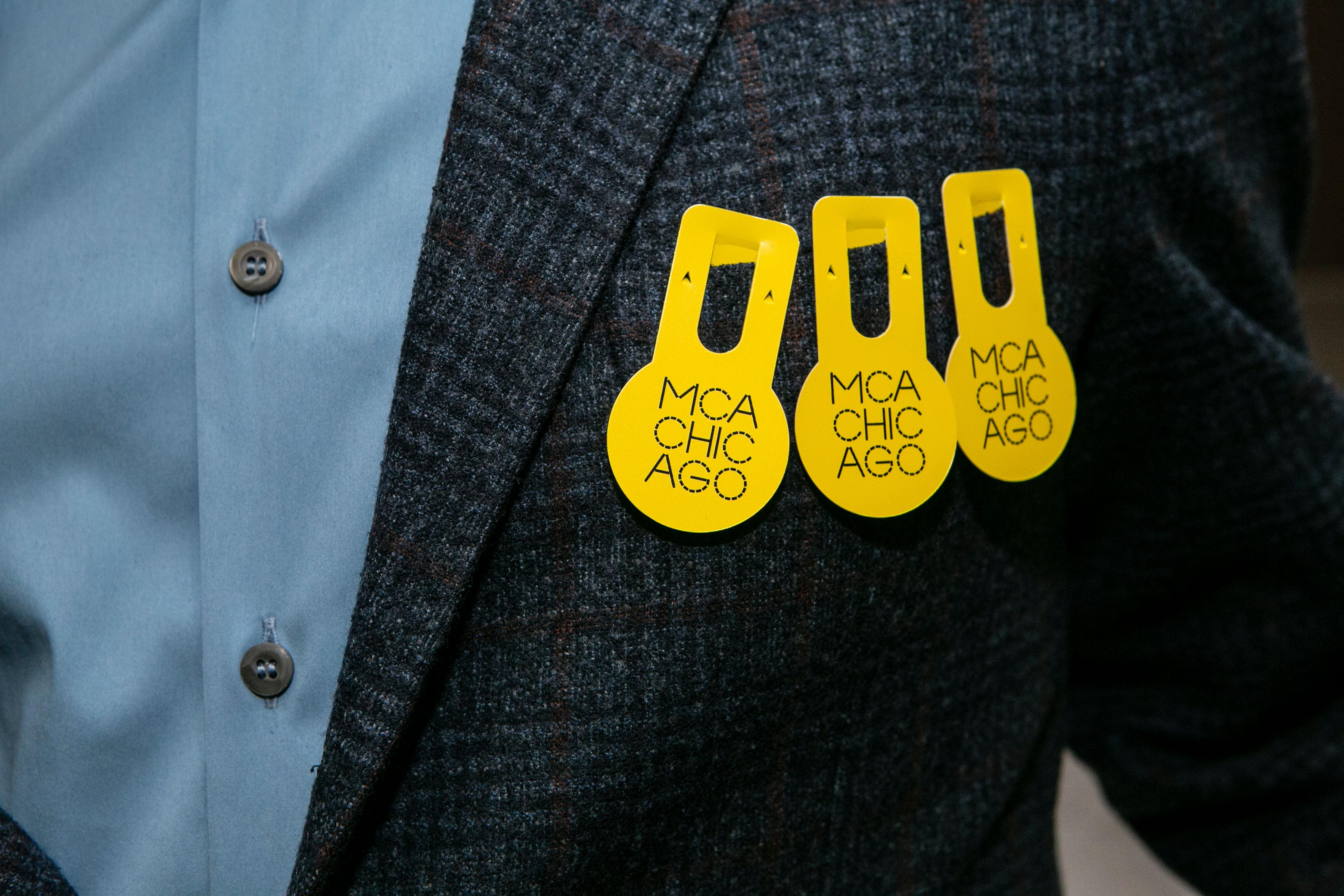 Close up of person in suit coat wearing 3 MCA Chicago admission badges