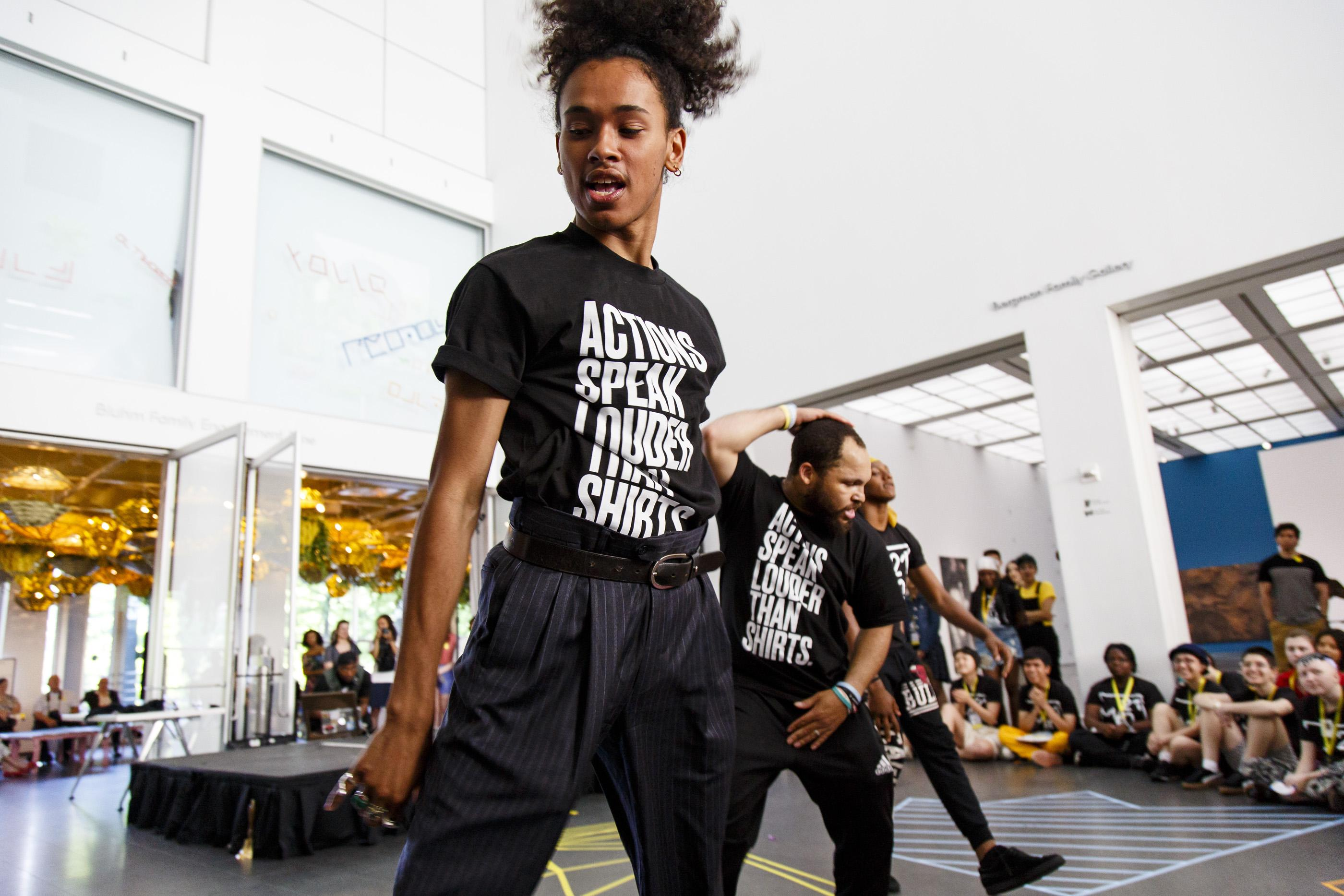 Three dancers perform in the MCA Atrium as dozens of audience members watch.