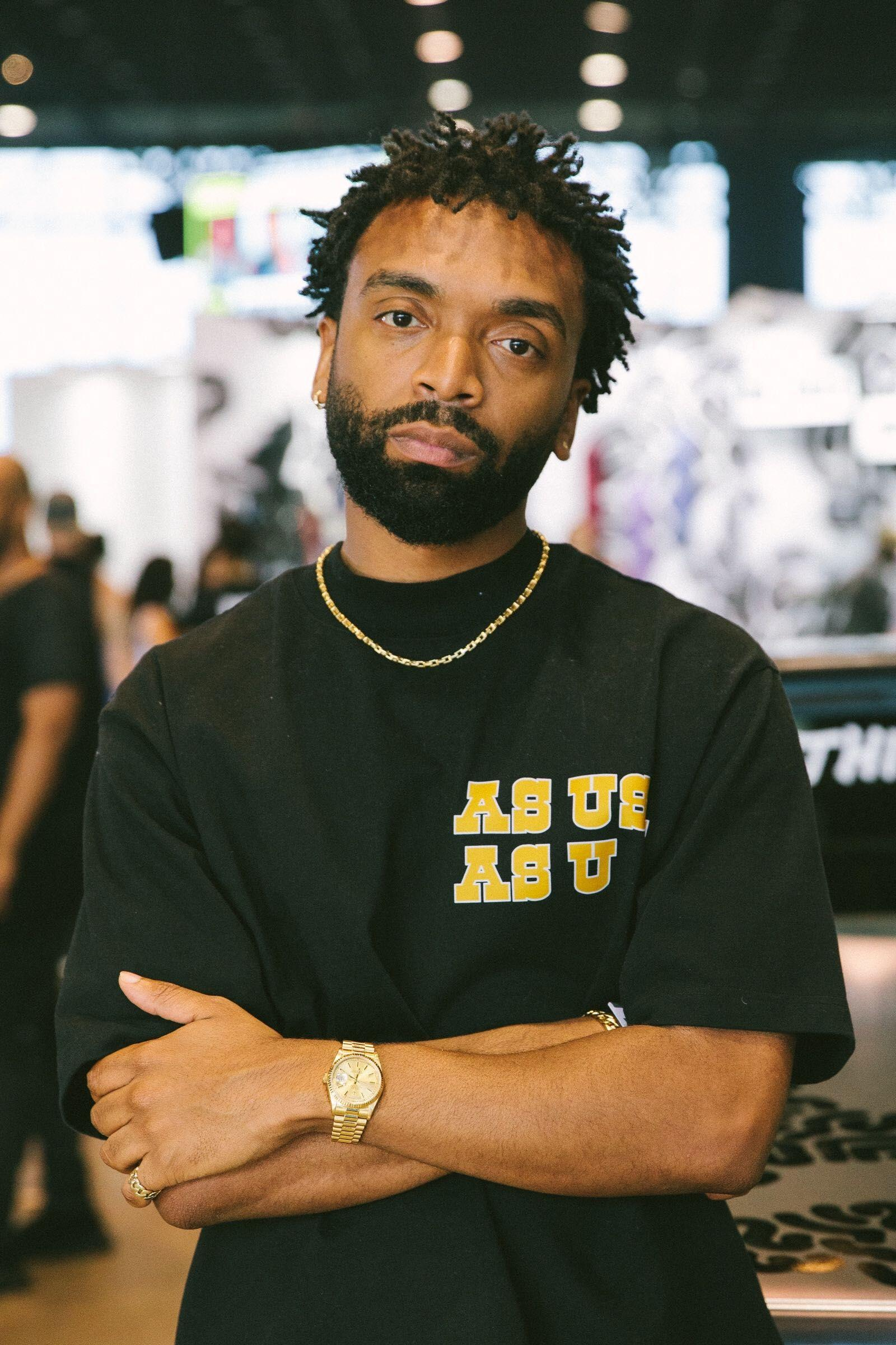 A person with short dreadlocks and a beard stands with arms crossed and head slightly tilted to their left while regarding the viewer with a serious expression.
