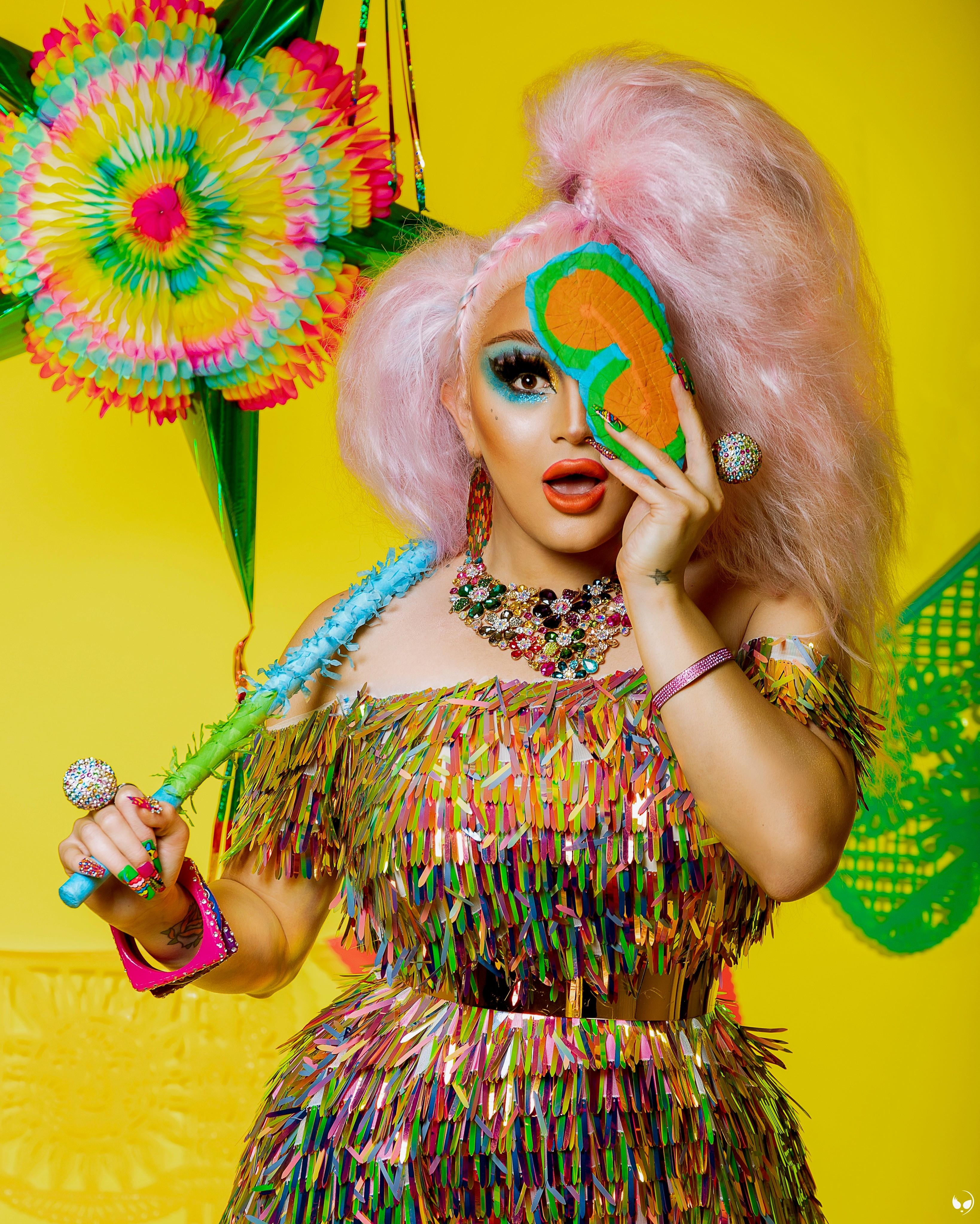 A person with big pink hair, dressed in colorful apparel, jewelry, and makeup, covers their left eye with a mask, with an expression of surprise.