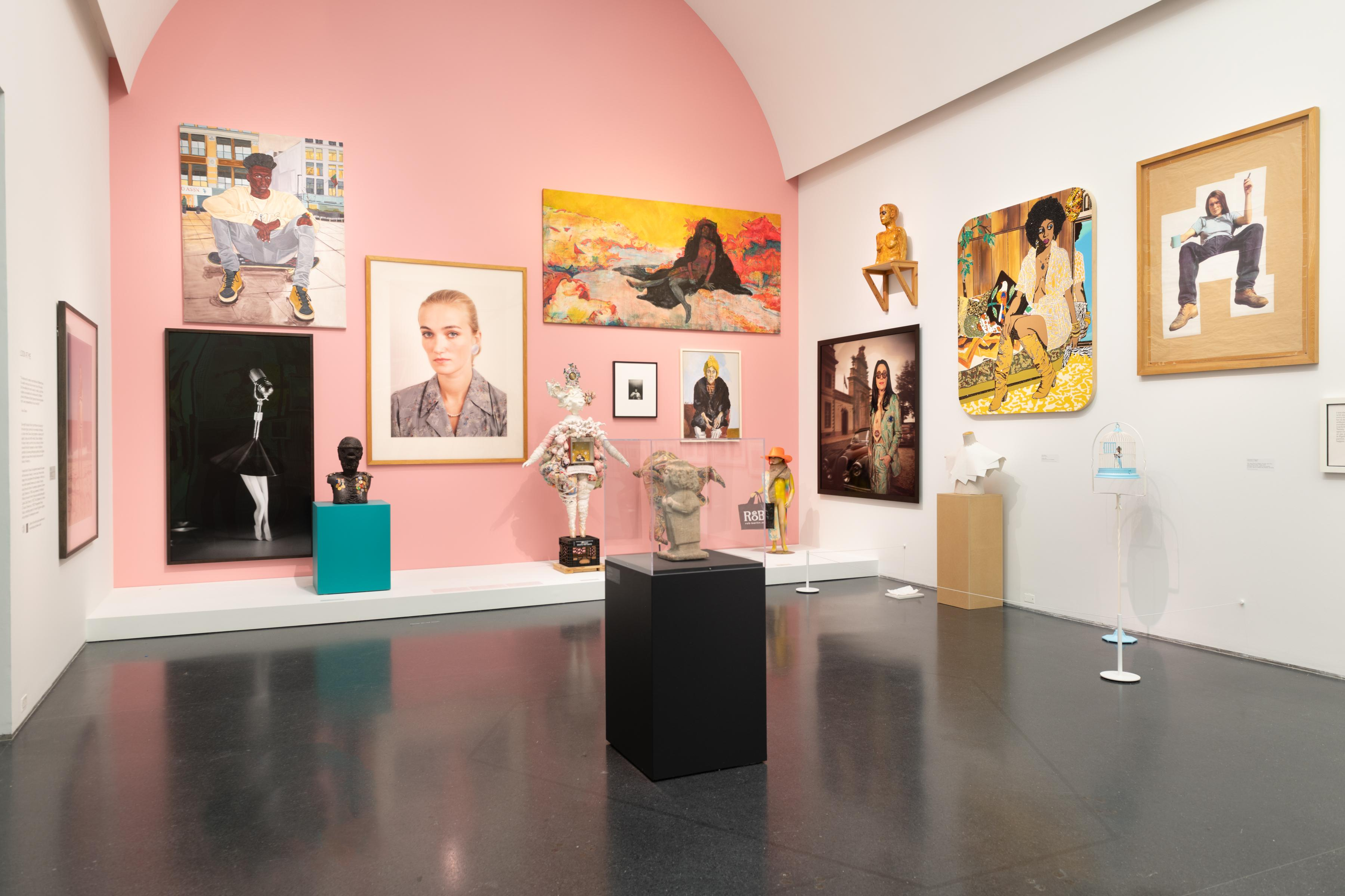 A pink, back wall is emphasized in a room with three walls shown. There are various paintings, photos and sculptures throughout the room.