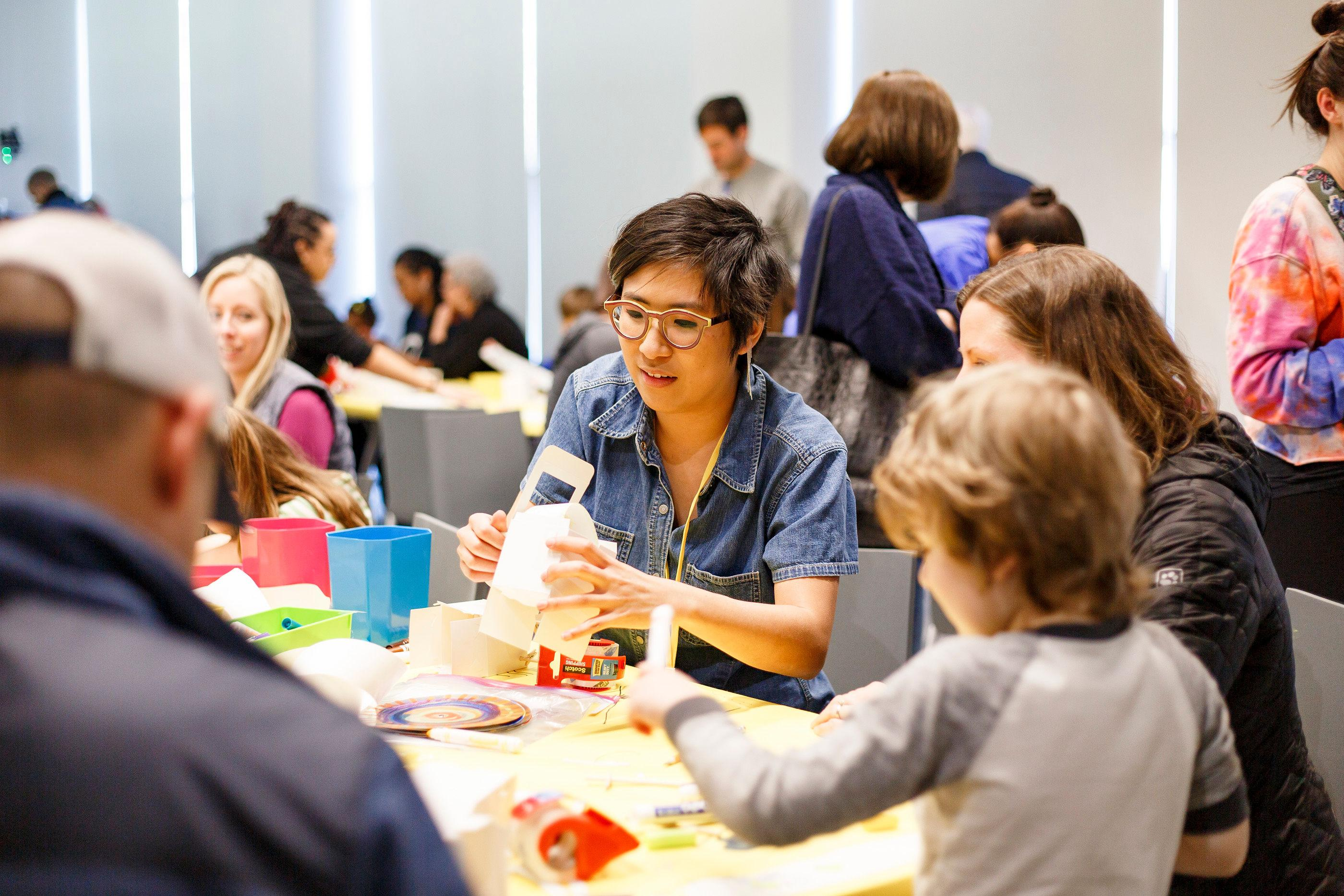 Smiling adults and children sit at tables creating objects with various material provided.