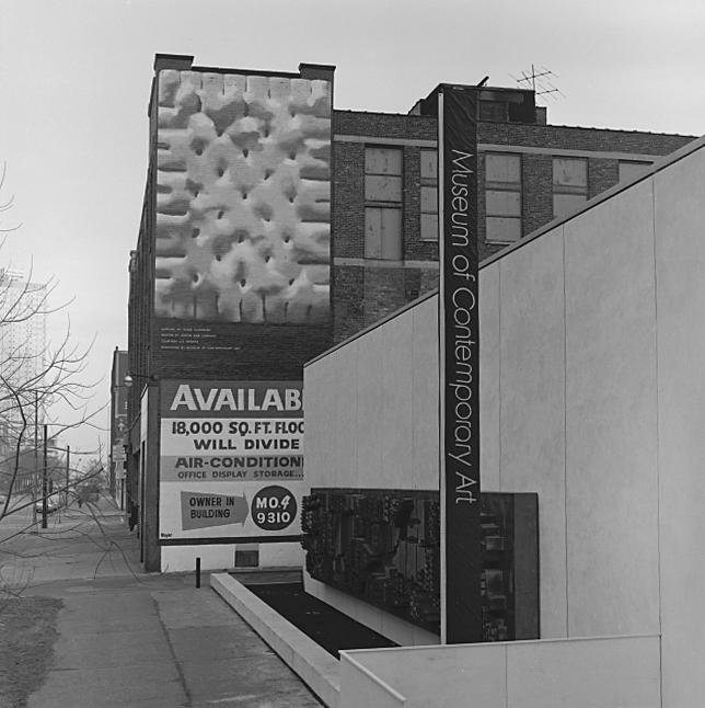 The exterior of a brick building beside a museum features a billboard depicting a gigantic soda cracker.