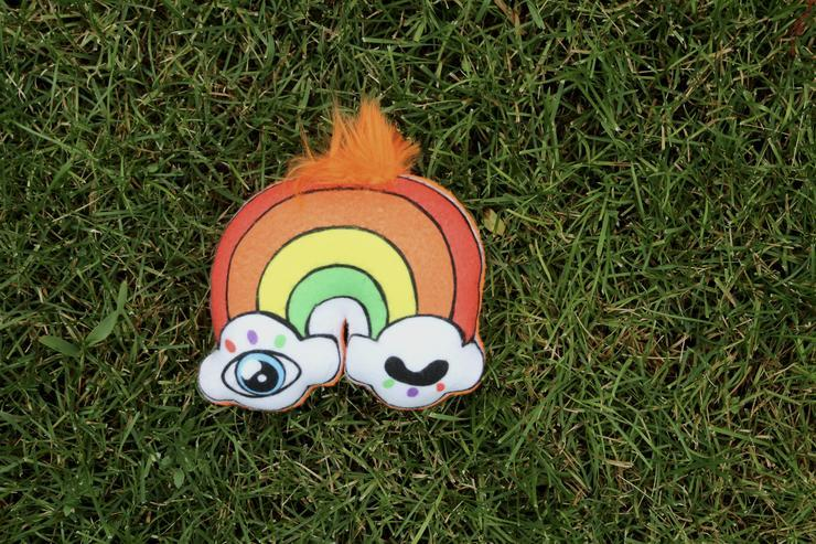 An orange rainbow with winky eye clouds on each end and a tuft of orange fluff on top lays on a bed of grass.