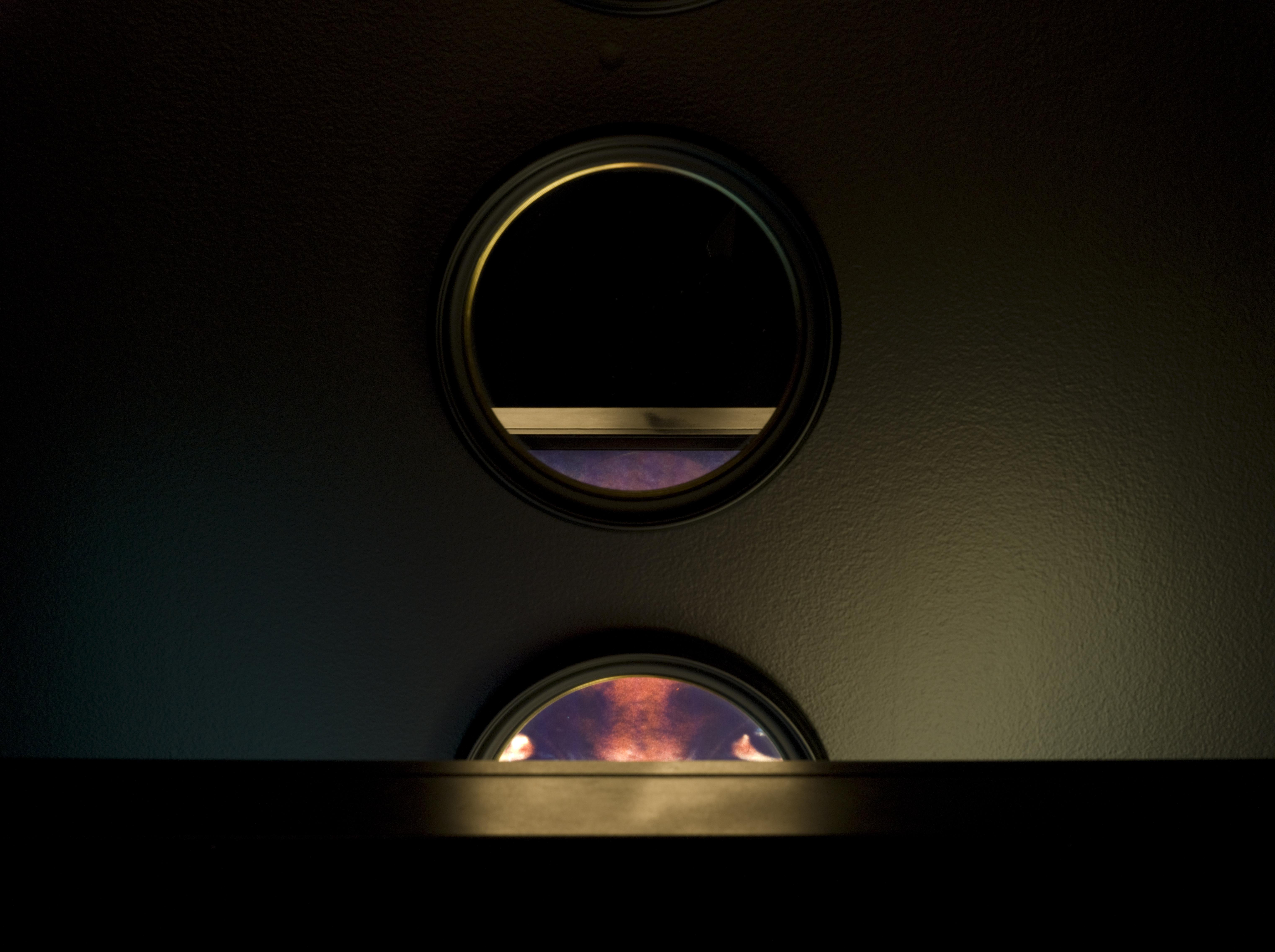 A dark view of a lightbox showing circular mirrors reflecting abstract colors of orange and purple