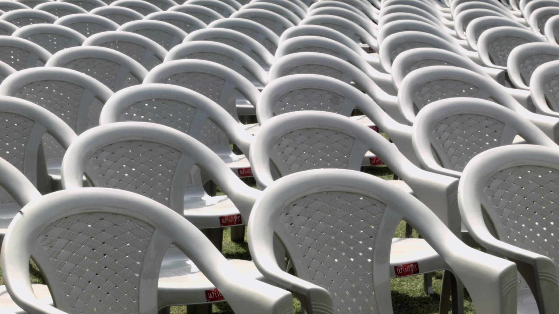 Plastic lawn chairs lined up fill the frame