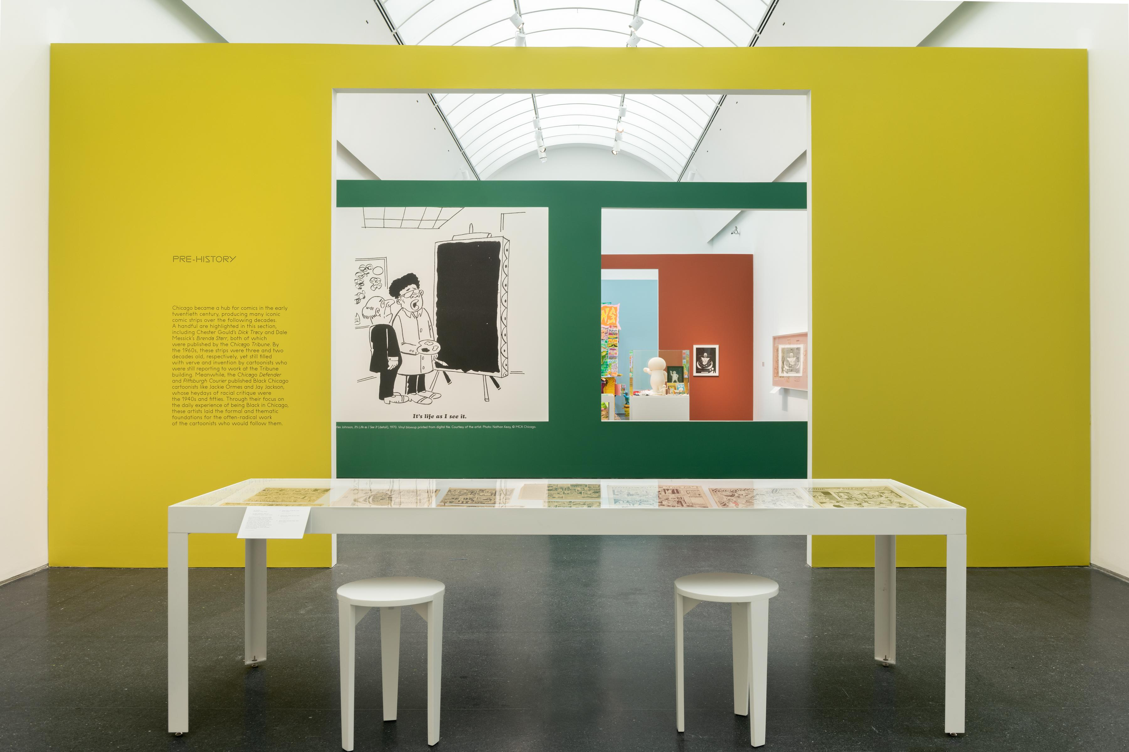 Exhibition interior showing a large white table with in front of a yellow wall with a doorway in the middle