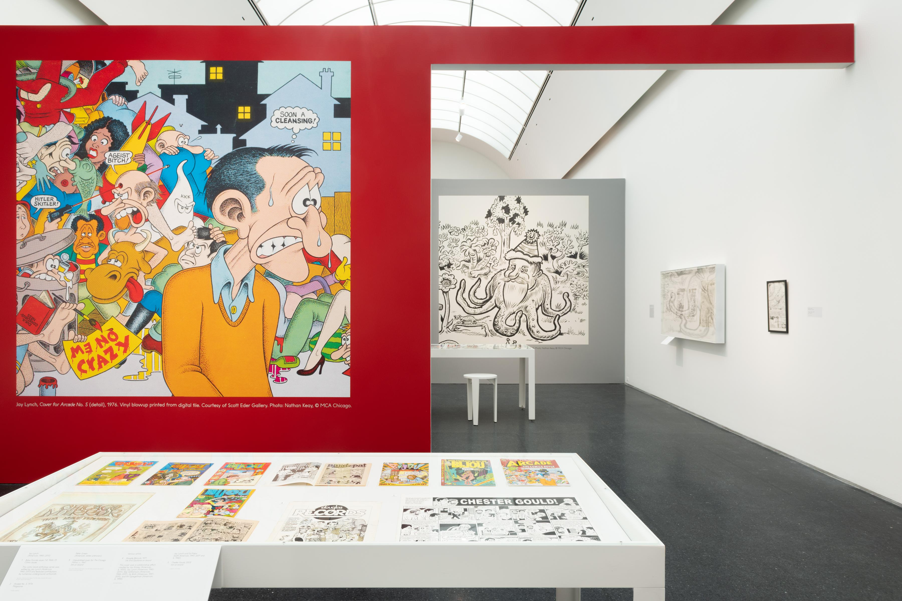 Exhibition interior with a large table and a bold, red wall with comic art depicting a sweating man